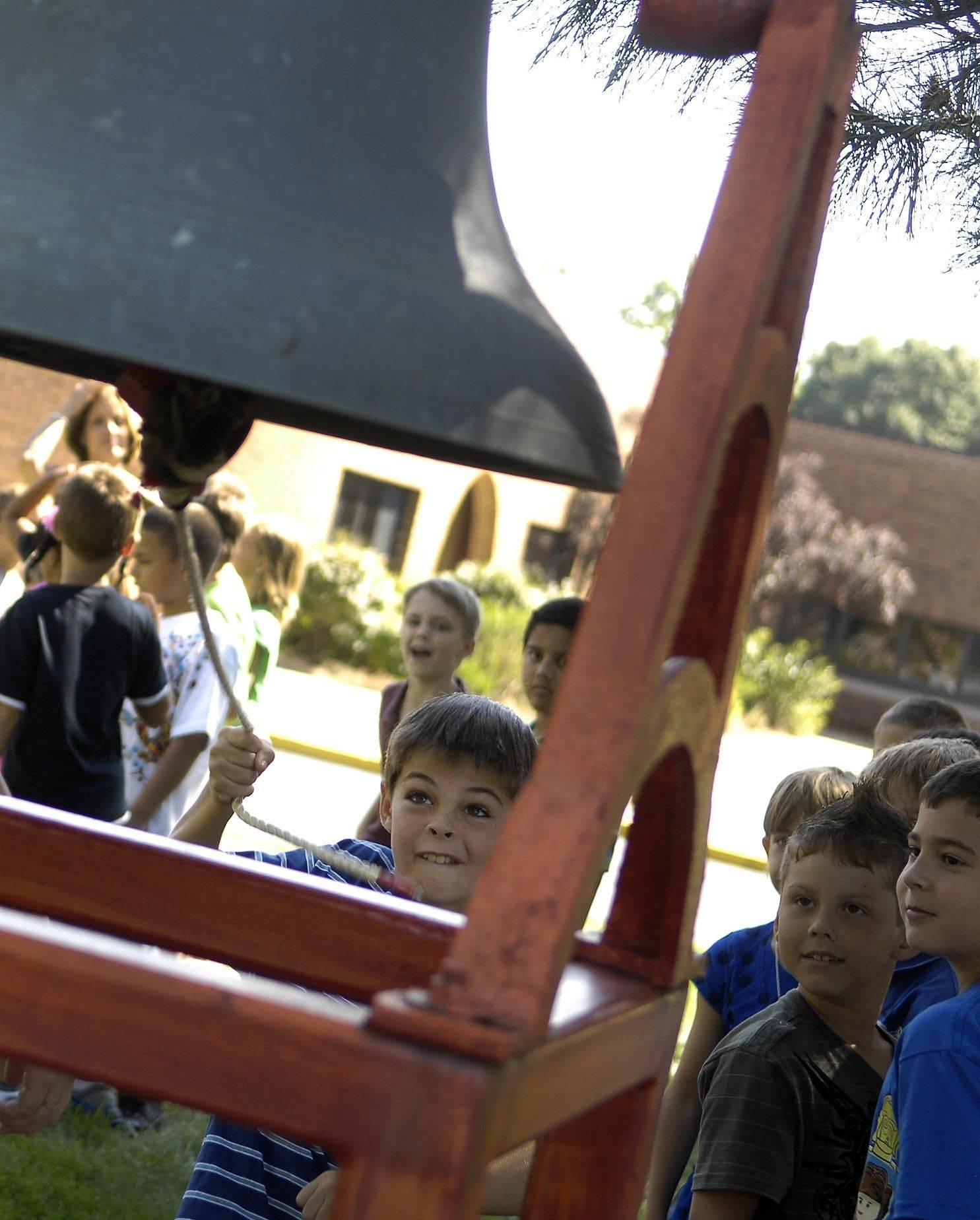 Third-grader Matthew Franzen gets his shot to ring the bell for the first day of school Wednesday at Louise White Elementary in Batavia. All 497 students got a chance to ring the bell, which dates to the 1890s.