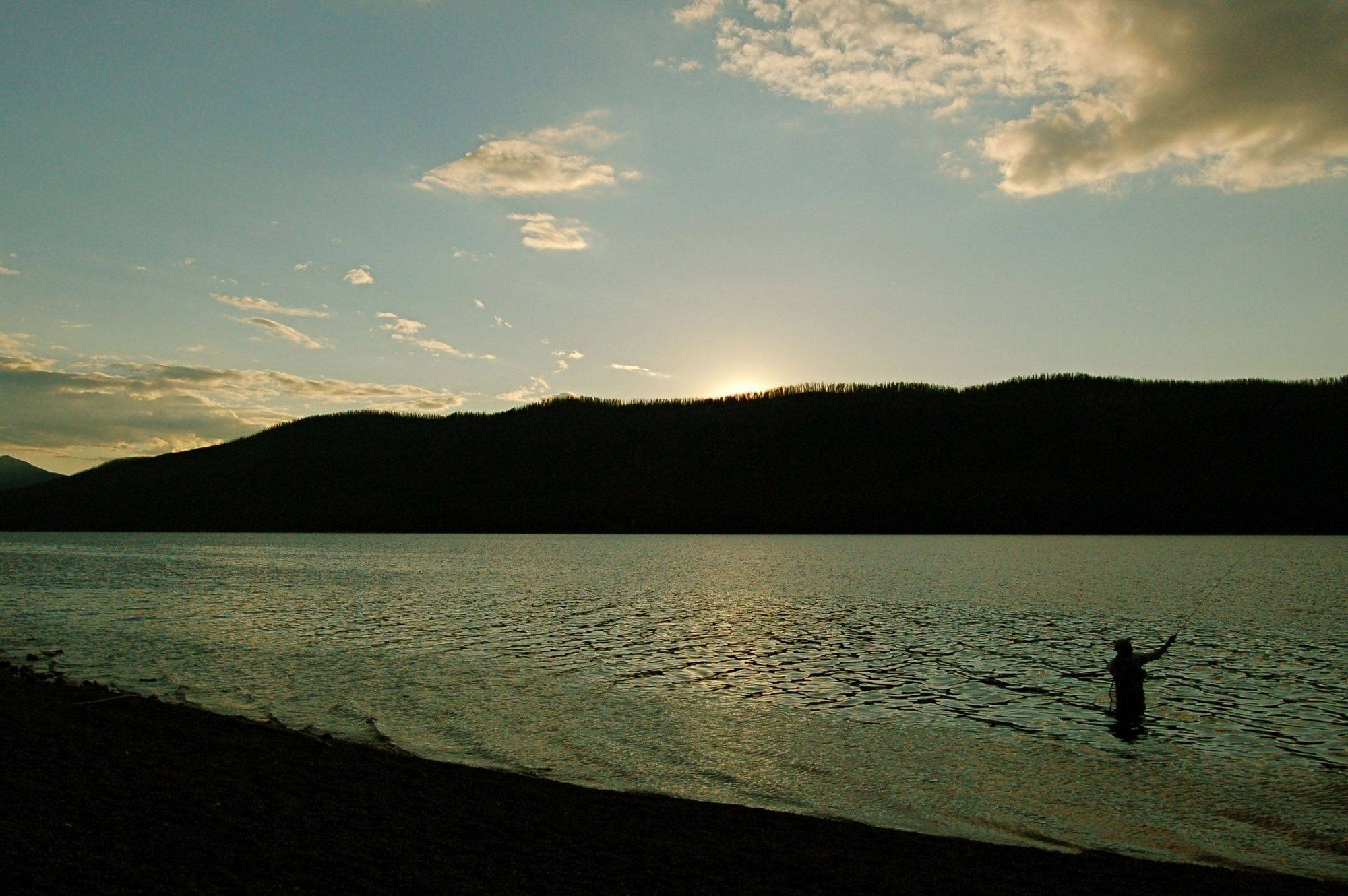 This picture was taken at Lake McDonald in Glacier National Park in September of 2008. For me the fly fisherman in silhouette made the picture.