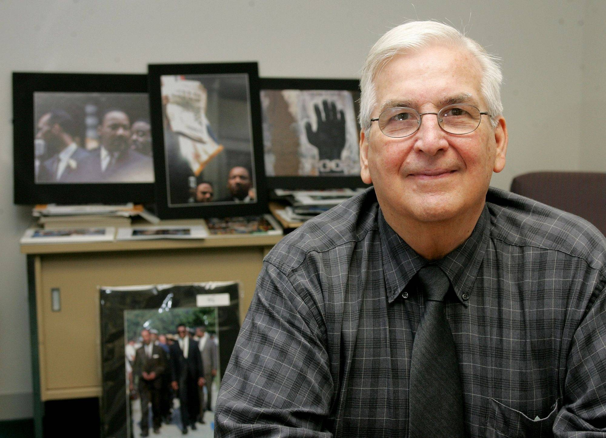 Bernie Kleina, executive director at HOPE Fair Housing Center in Wheaton, in his office with photos he took of the Civil Rights Movement in the background.
