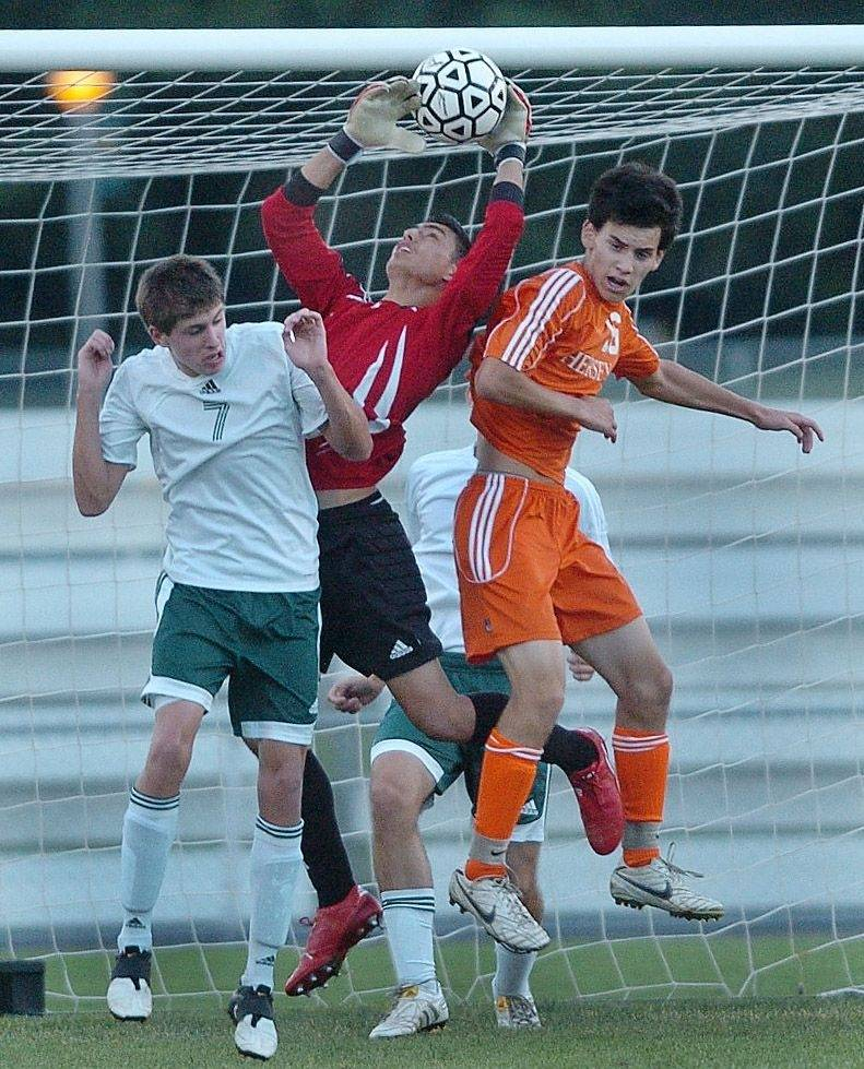 Elk Grove goalkeeper Frankie Ortiz makes a save surrounded by teammate Matt Ginter, left, and Hersey midfielder Brian Tanser during Hersey at Elk Grove boys soccer game Monday.