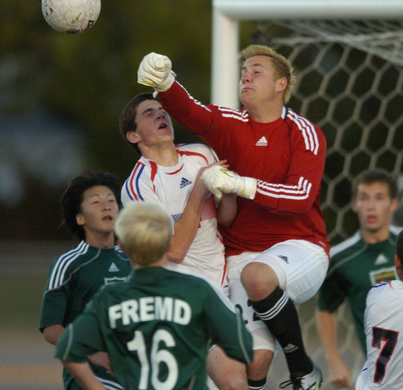 Fremd goalkeeper Scott Sutarik bats the ball away as Conant's Joey Bosco makes contact during Tuesday's game.