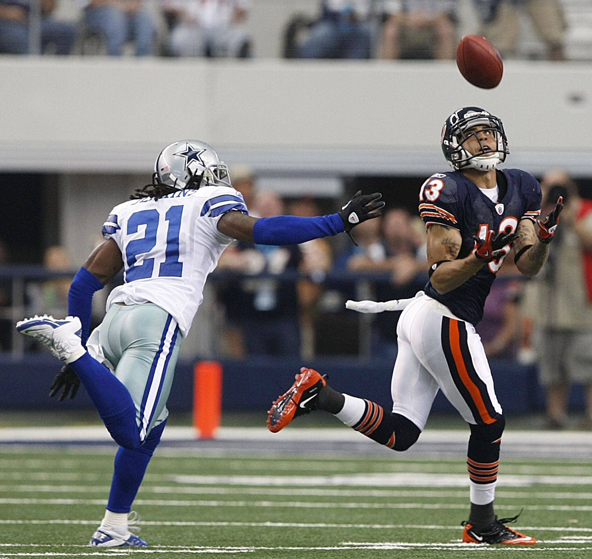 Chicago Bears wide receiver Johnny Knox (13) catches a long pass from Jay Cutler for a first down, next to Dallas Cowboys cornerback Mike Jenkins (21) during the first half.