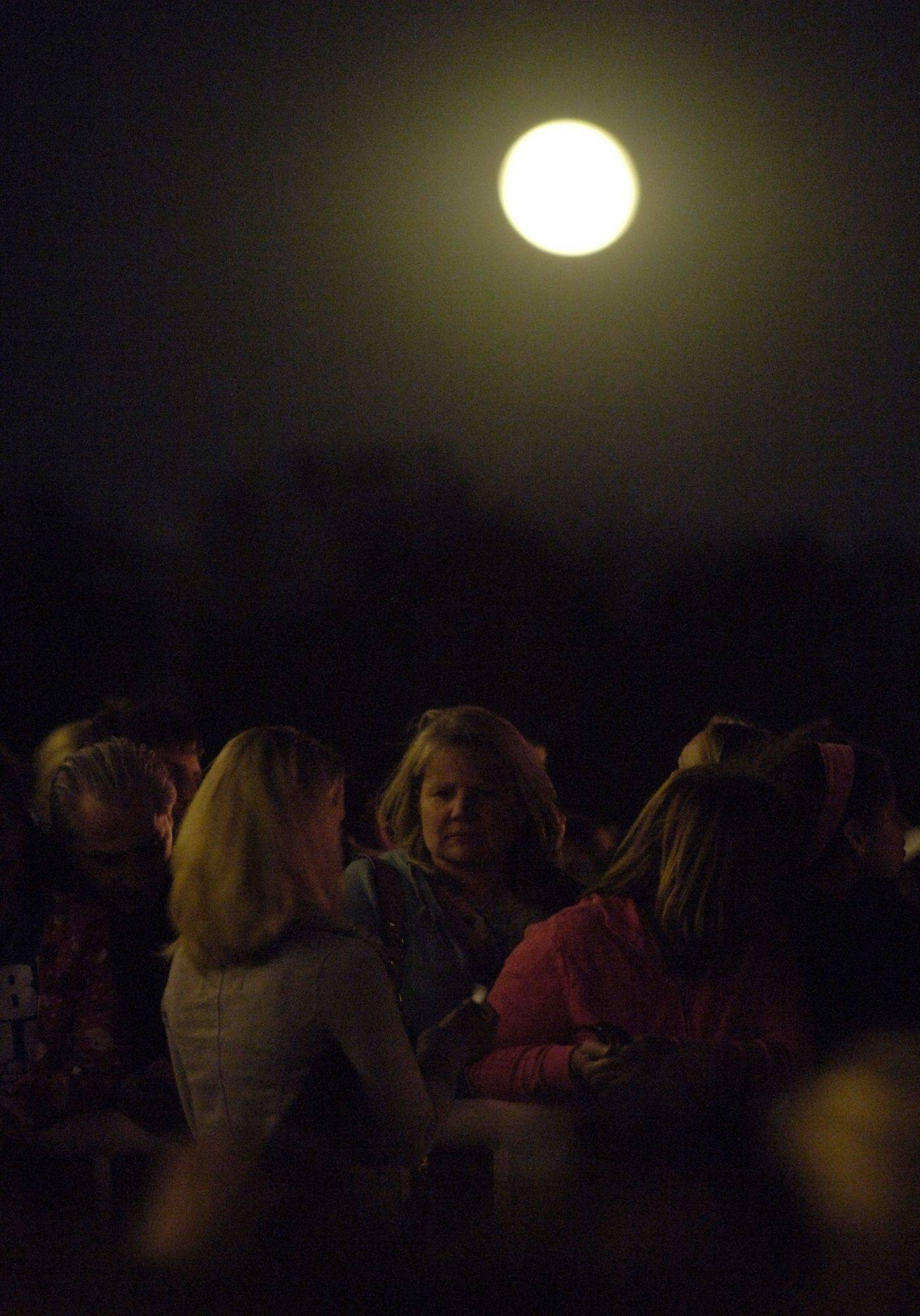 The moon rises while fans wait for the start of the Lee Dewyze concert at Arlington Park Friday evening.