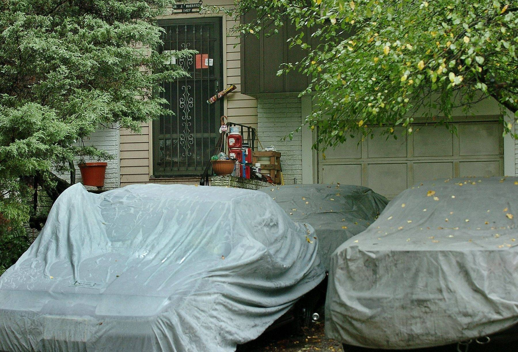 Three cars sit covered in the driveway of John Wuerffel's house on the 1400 block of Hampton Lane in Schaumburg since he began his clean up efforts this month.