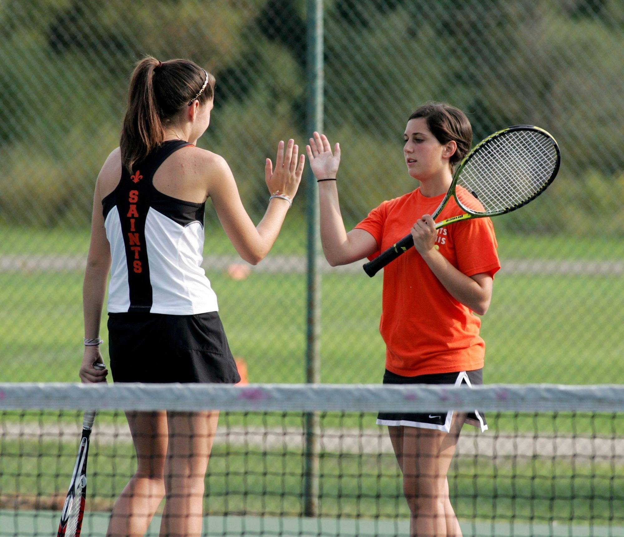 St. Charles East's Erin Bowman, right, with partner Claire Hafner earlier this year against St. Francis, recently won her 100th career match for the Saints.