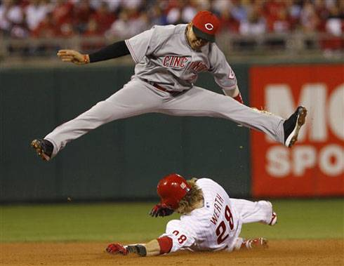 Cincinnati Reds shortstop Orlando Cabrera jumps over Philadelphia Phillies' Jayson Werth after forcing him out at second base and turning a double play during the fourth inning of Game 2 of baseball's National League Division Series, Friday