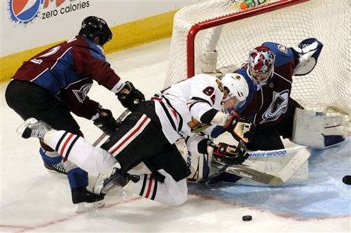 Colorado Avalanche defenseman Scott Hannan (22) trips Chicago Blackhawks  center Tomas Kopecky (82) as Avalanche goalie Craig Anderson (41) watches the puck during the second period of an NHL hockey game Thursday.