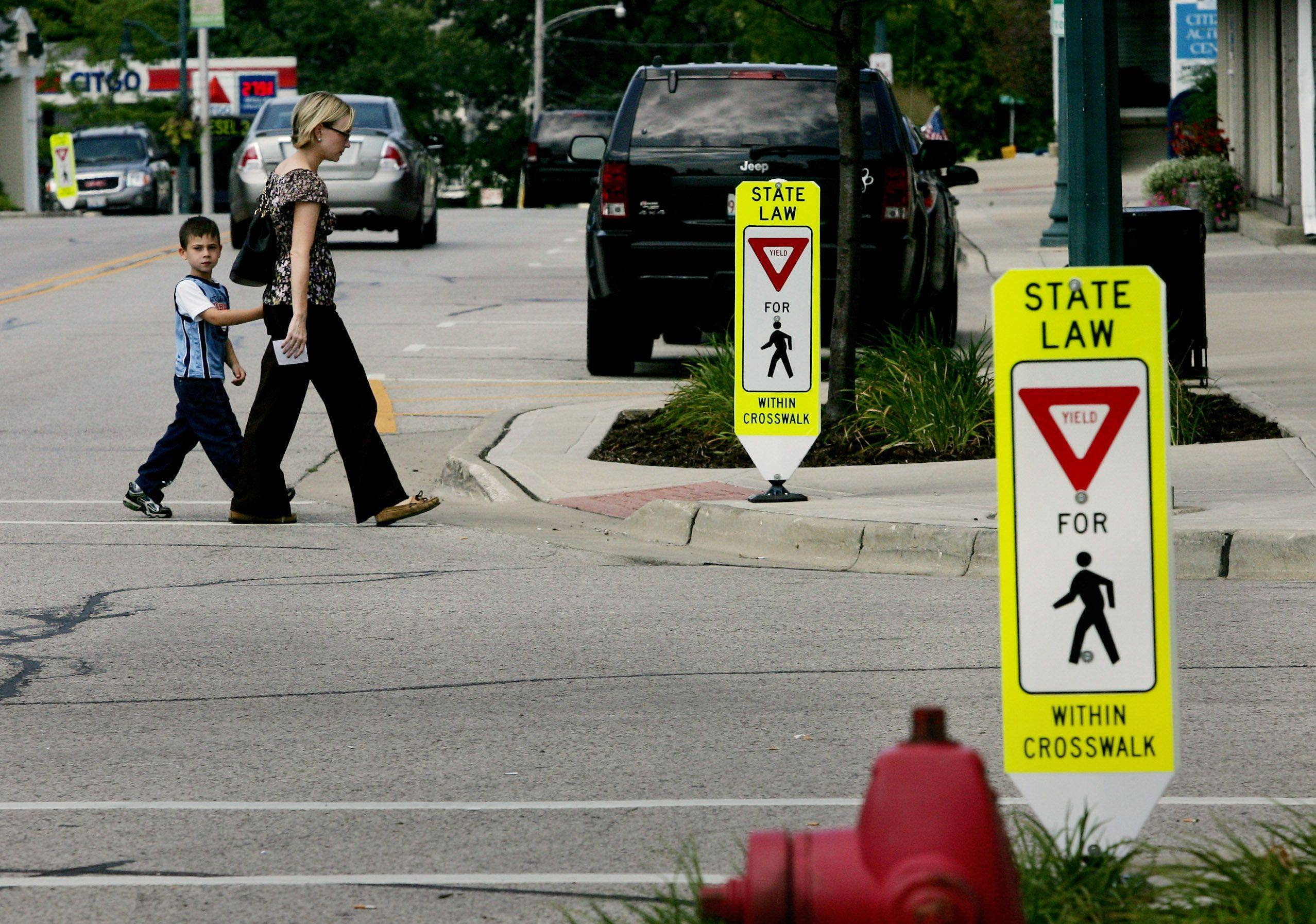 Gilbert R. Boucher II/gboucher@dailyherald.comEmilie Kaplan and her 5-year-old nephew, Zakai, of Island Lake, are near crosswalk signs along Main Street in Wauconda. Some towns already have changed the yield image to a stop, reflecting Illinois' new crosswalk law.
