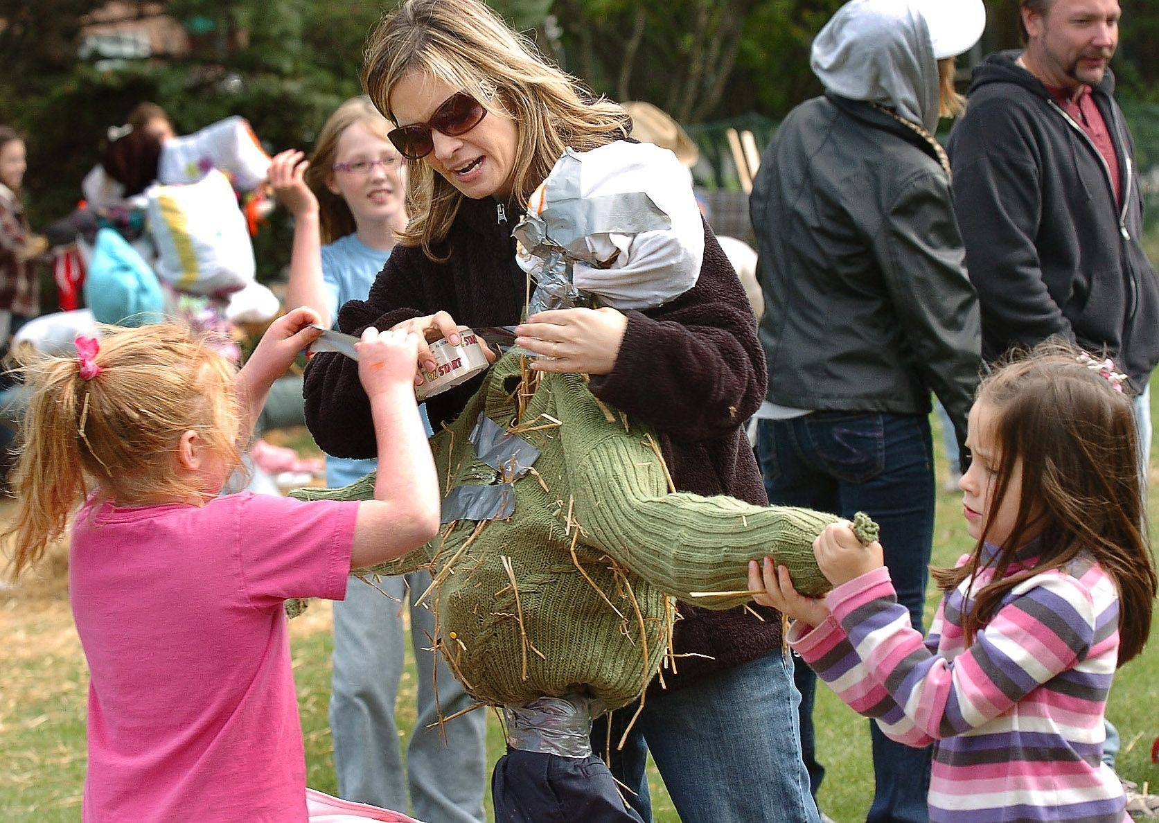 Erin Trunda, middle, works on a scarecrow for the scarecrow competition with Rebecca Caliendo, left, and Katie Trunda during the Arlington Heights Autumn Harvest.