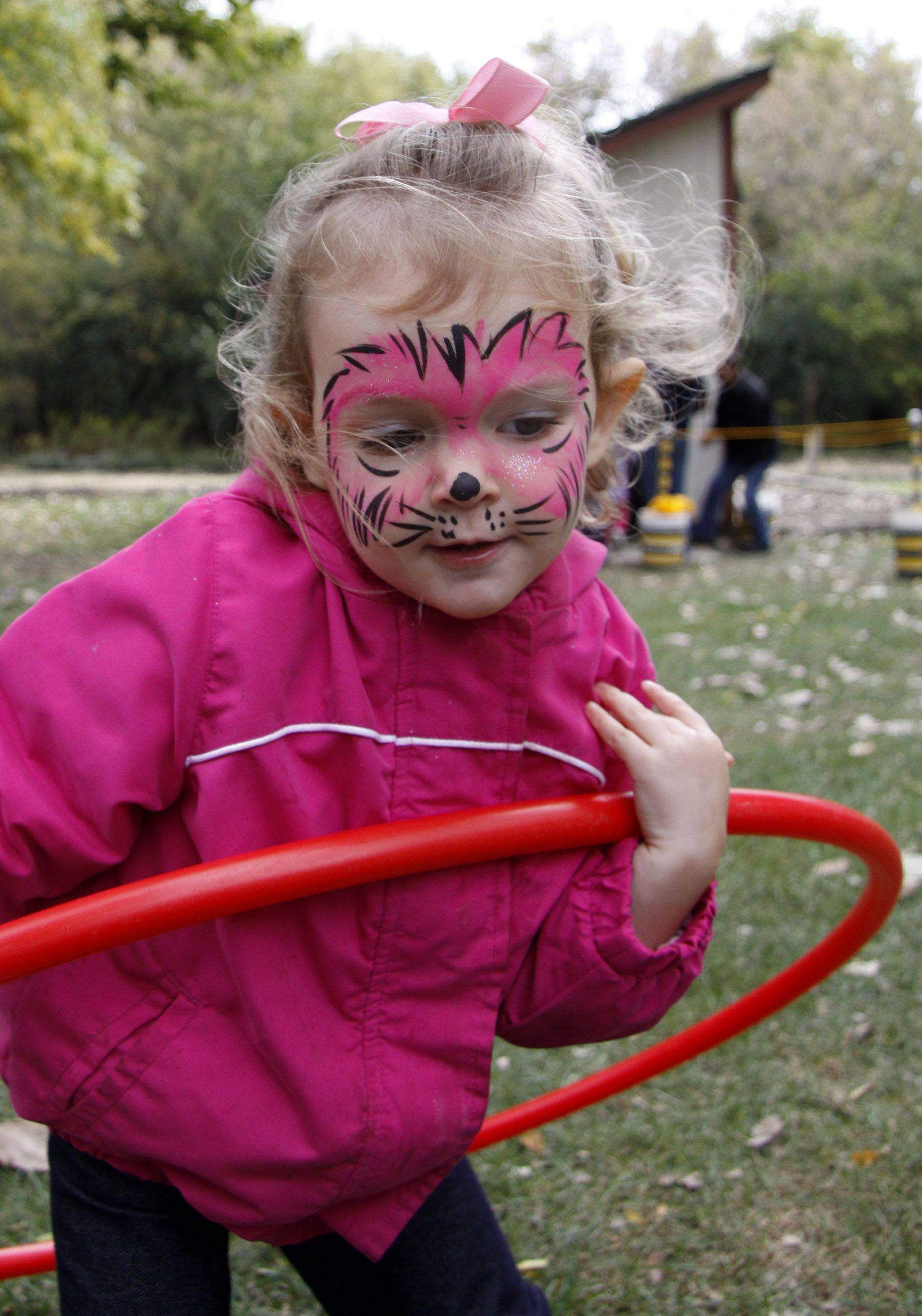Sophia Kederhauser, 2, of Warrenville, tries out a hula hoop at the Fischer Farm Heritage Day and Bensenville Park District's 50th anniversary Saturday in Bensenville. The event was free and open to the public. Fischer Farm is the oldest remaining homestead in DuPage County.