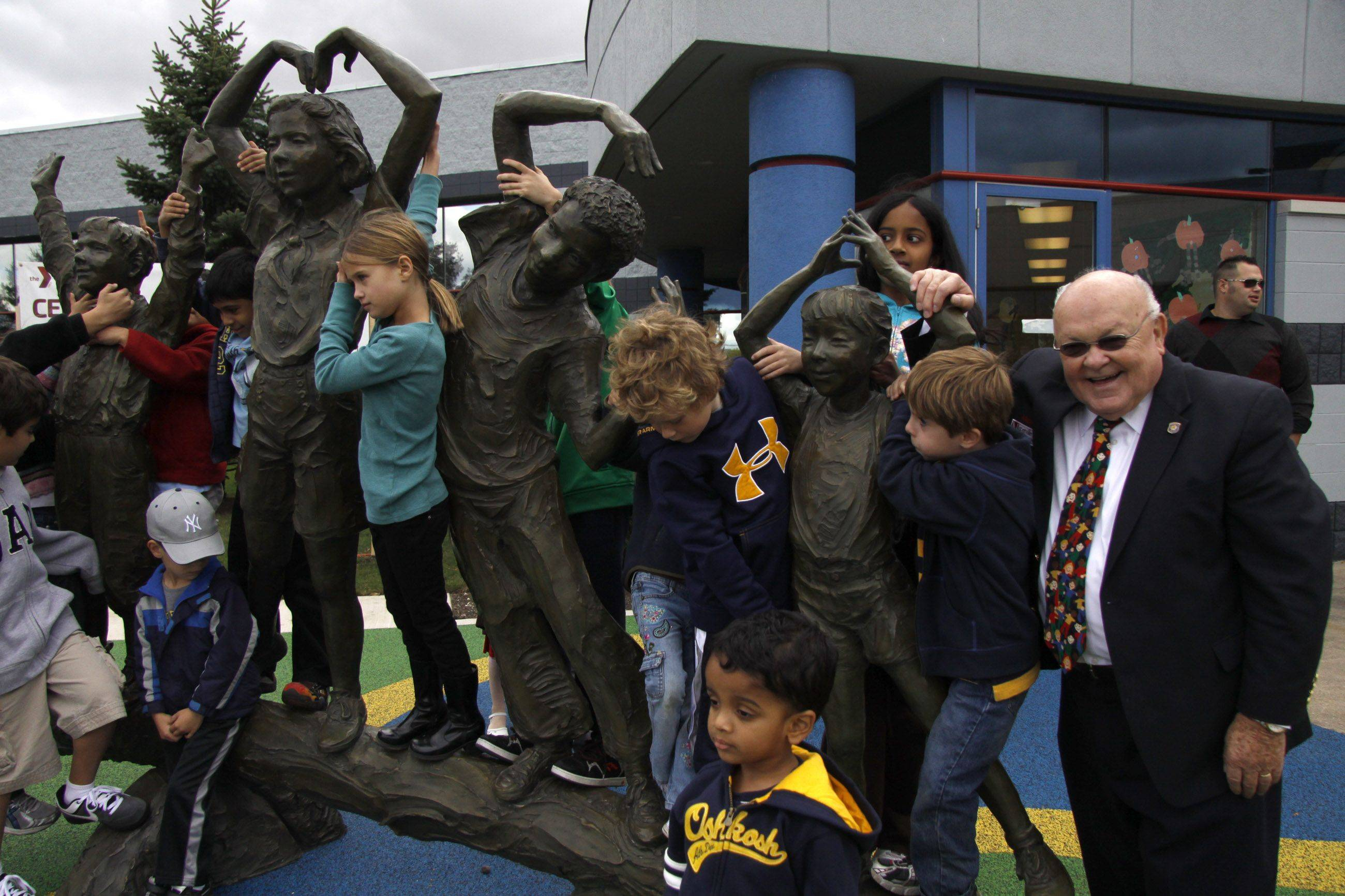 The unveiling of the new Century Walk YMCA statue was held Sunday at Fry Family YMCA in Naperville. Naperville Mayor George Pradel poses for a shot next to the new statue. Children are encouraged to climb on the 1500 lb work of art.