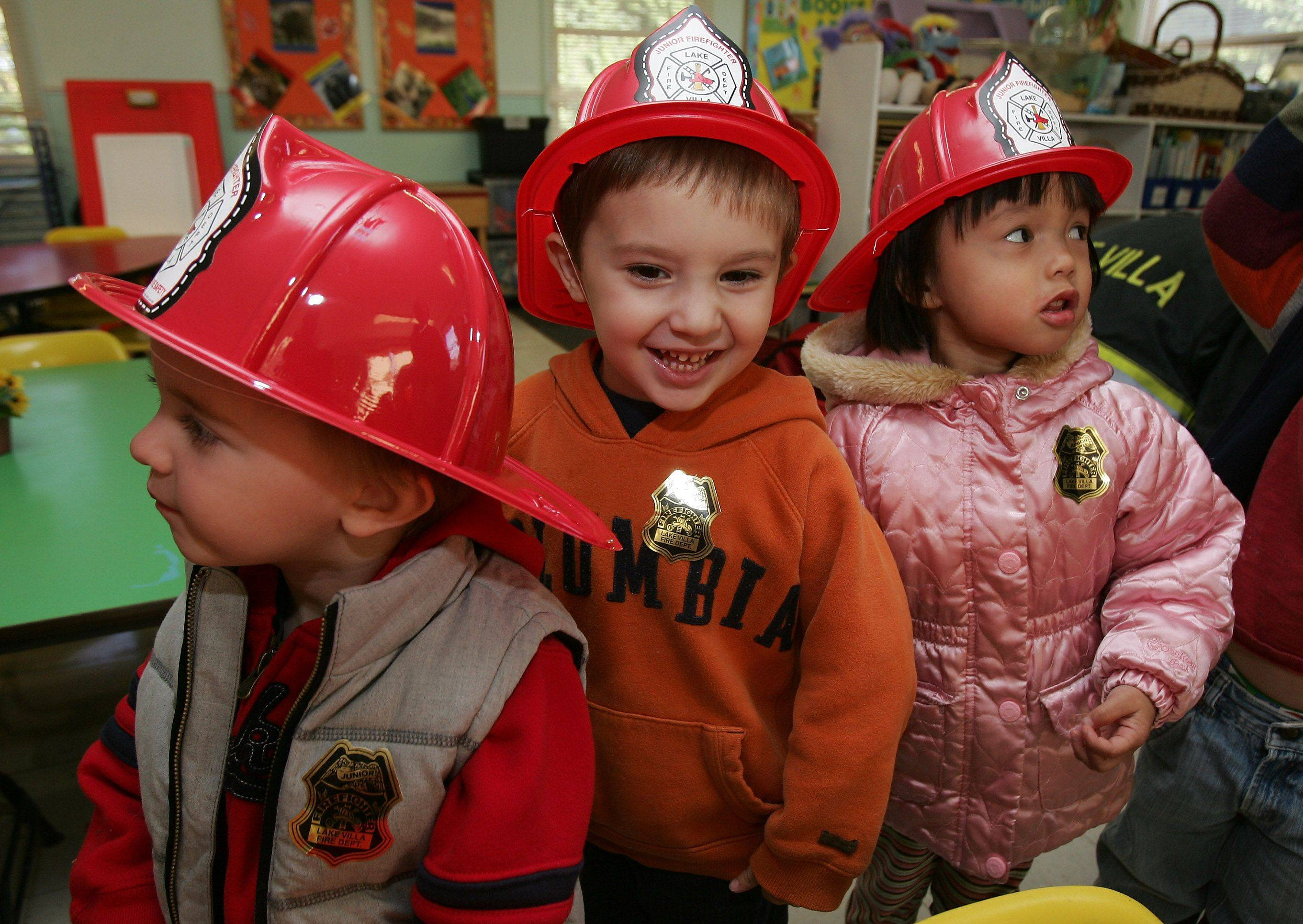 Jack Murray, left, Spencer Reed, and Catelyn Dayao of Toni Levy's 3 to 4-year-old class laugh while wearing new firefighters' hats during a visit by Lake Villa firefighter Greg Phillips to the Lindenhurst Early Childhood Center Monday during Fire Prevention Week.