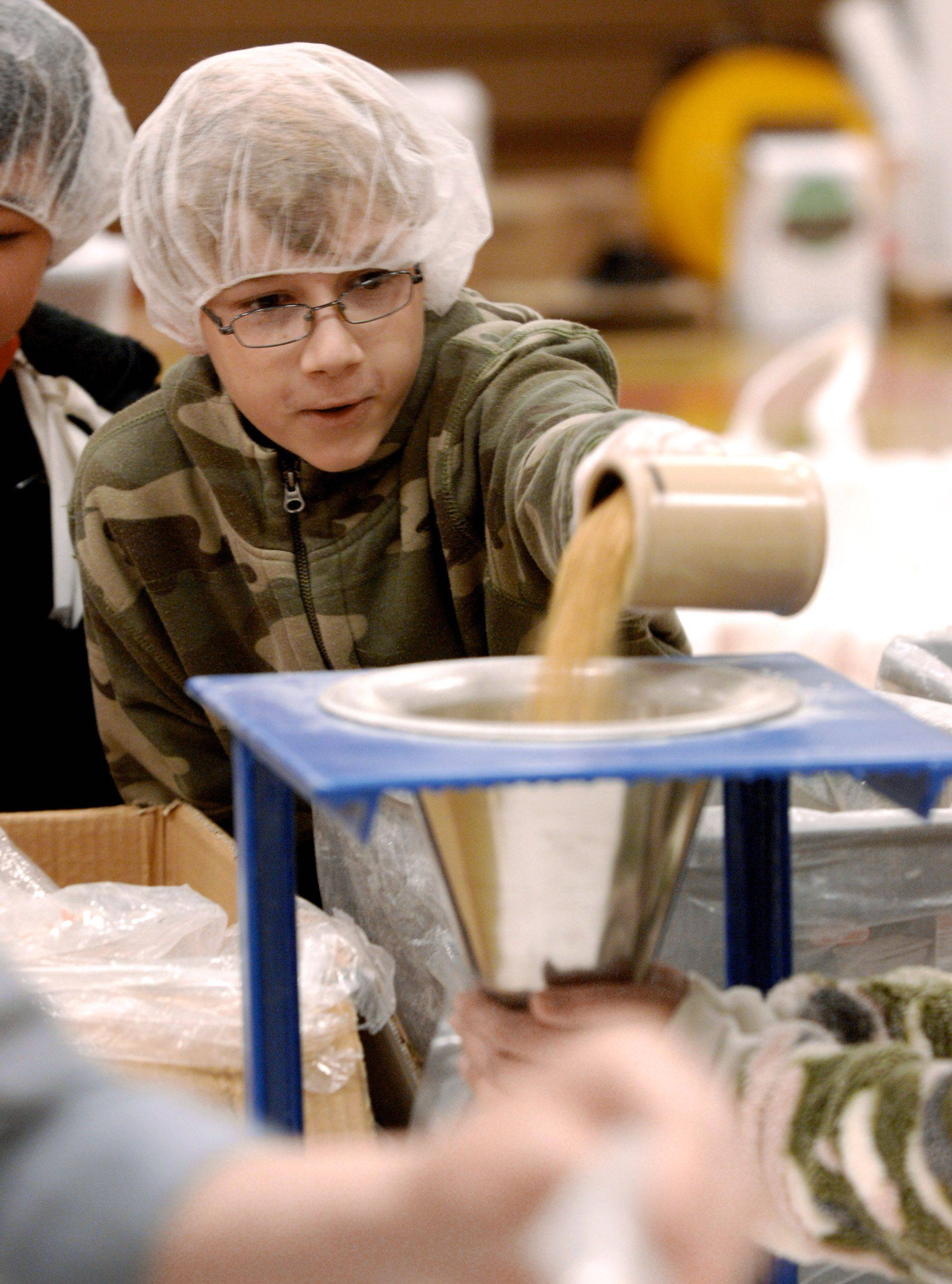Nick Coser pours in the soy component as he participates in packing food for Feed My Staving Children at St. Peters School in Arlington Heights, to finish out a weekend of packing by seven area churches. Seven churches packed over 175,000 meals.