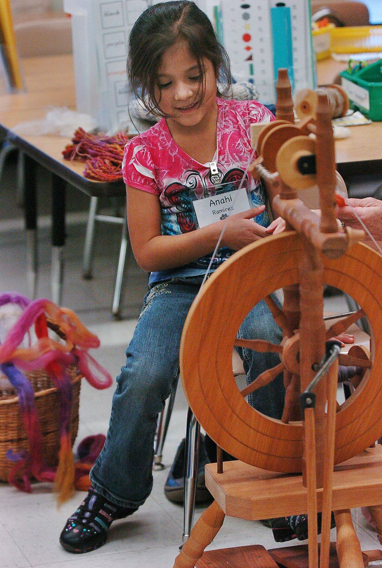 Woodland Primary School kindergartner Anahi Ramirez tries out the spinning wheel of presenter Allison Ashley, who was visiting Woodland to demonstrate the art of spinning yarn from wool.
