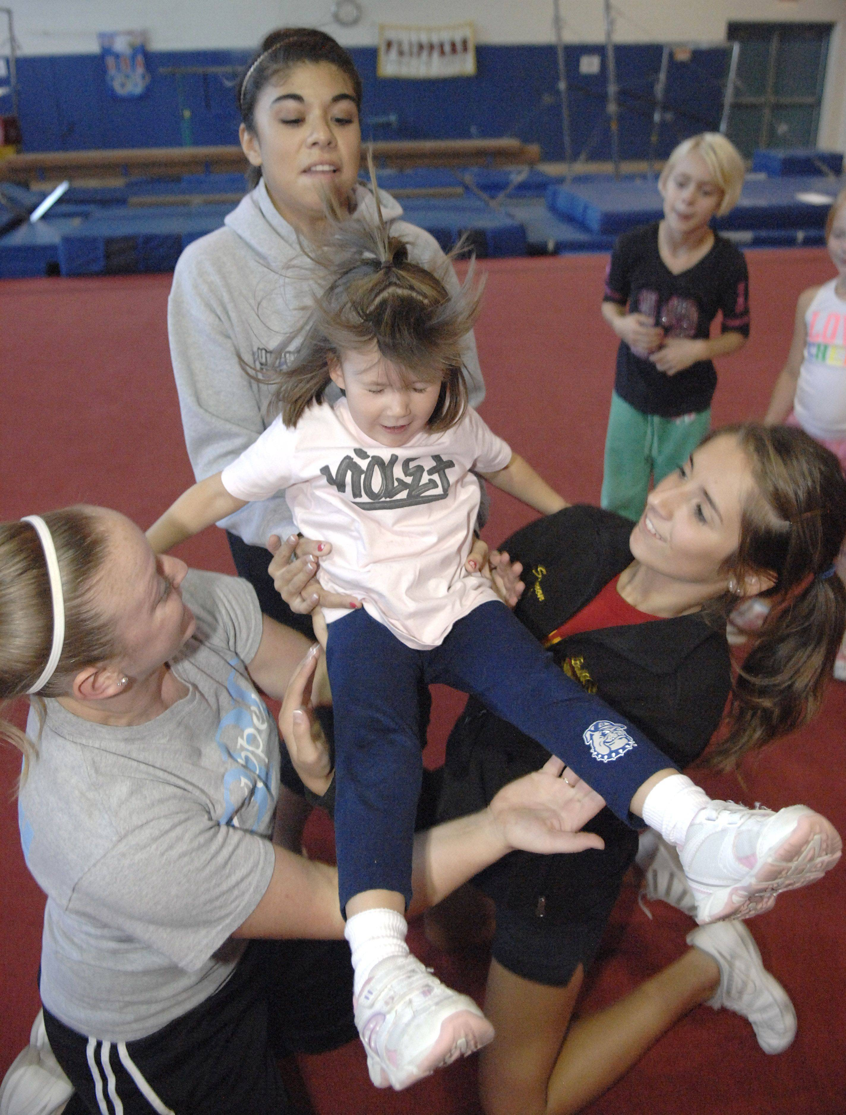Cheer coaches Bethanne LaFleur, Lilly Garcia and Shannon McGee catch Violet Carlson, 4, of Batavia while doing a pop-up at the Batavia Park District's cheer class for young girls.