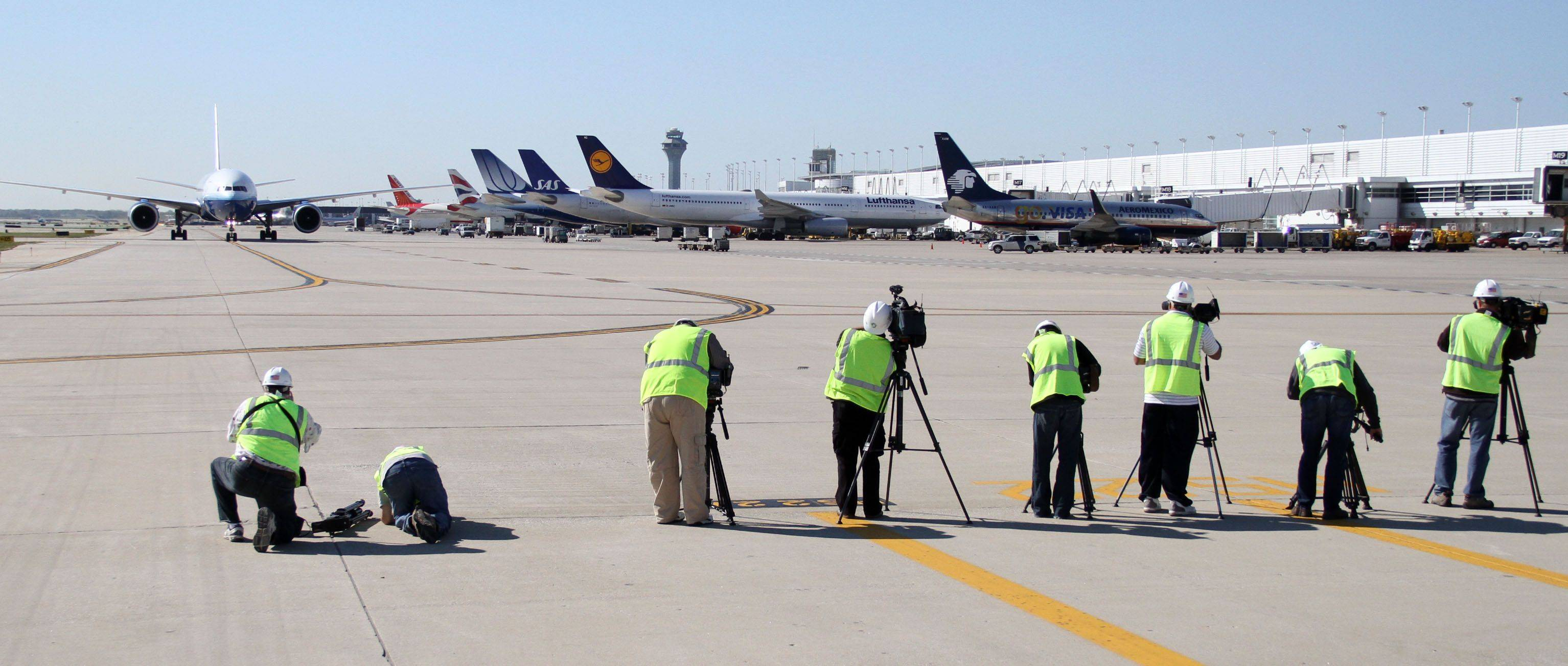 Chicago area TV station video photographers work at International Terminal 5 during a moderation project media tour at O'Hare International Airport Tuesday, October 5. The photographers were required to wear vests, hard hats and safety glasses while updating file video of the 10 Center East construction.