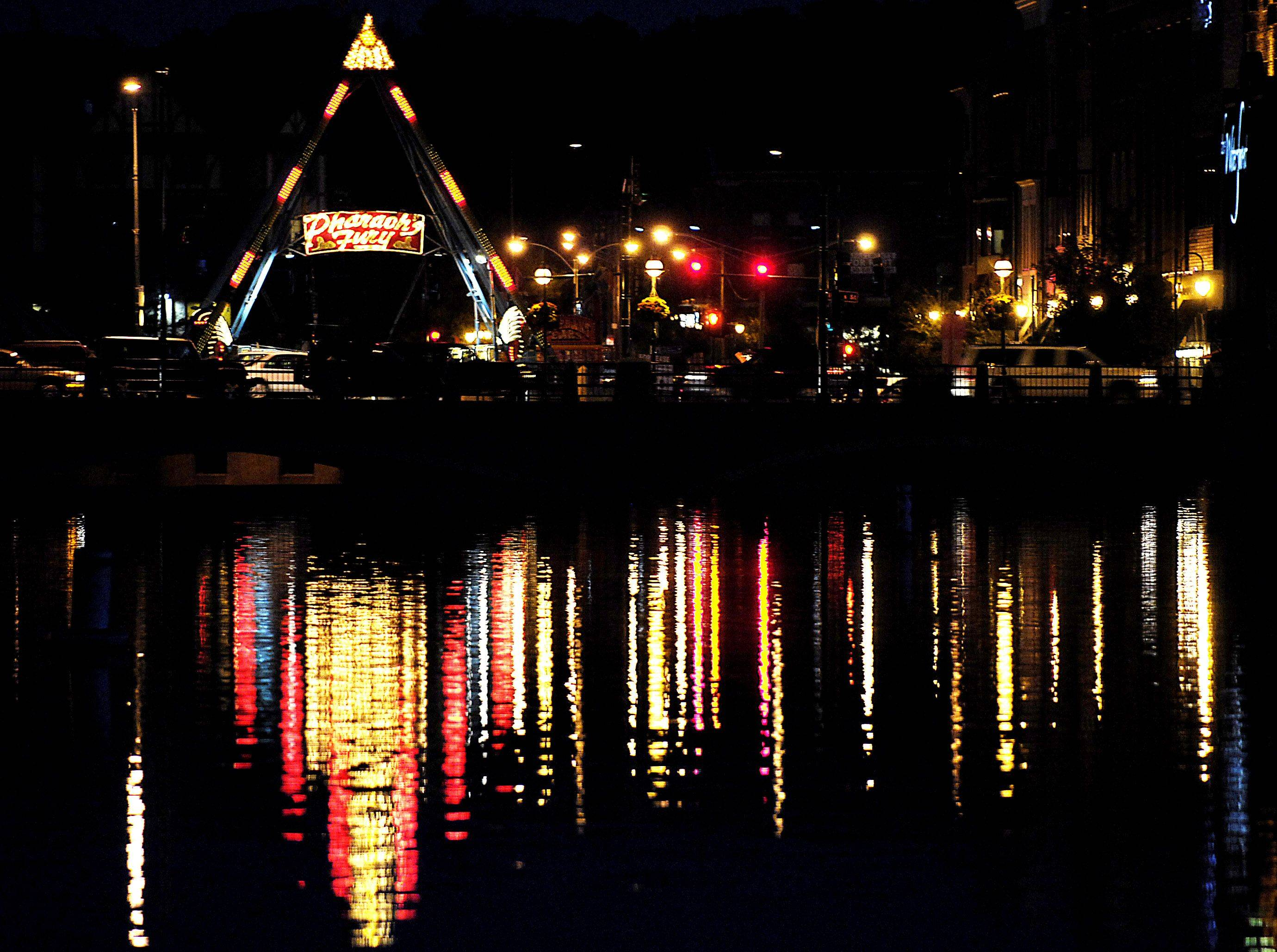 Lights reflect on the Fox River as the annual Scarecrow Festival sets up Tuesday in St. Charles.