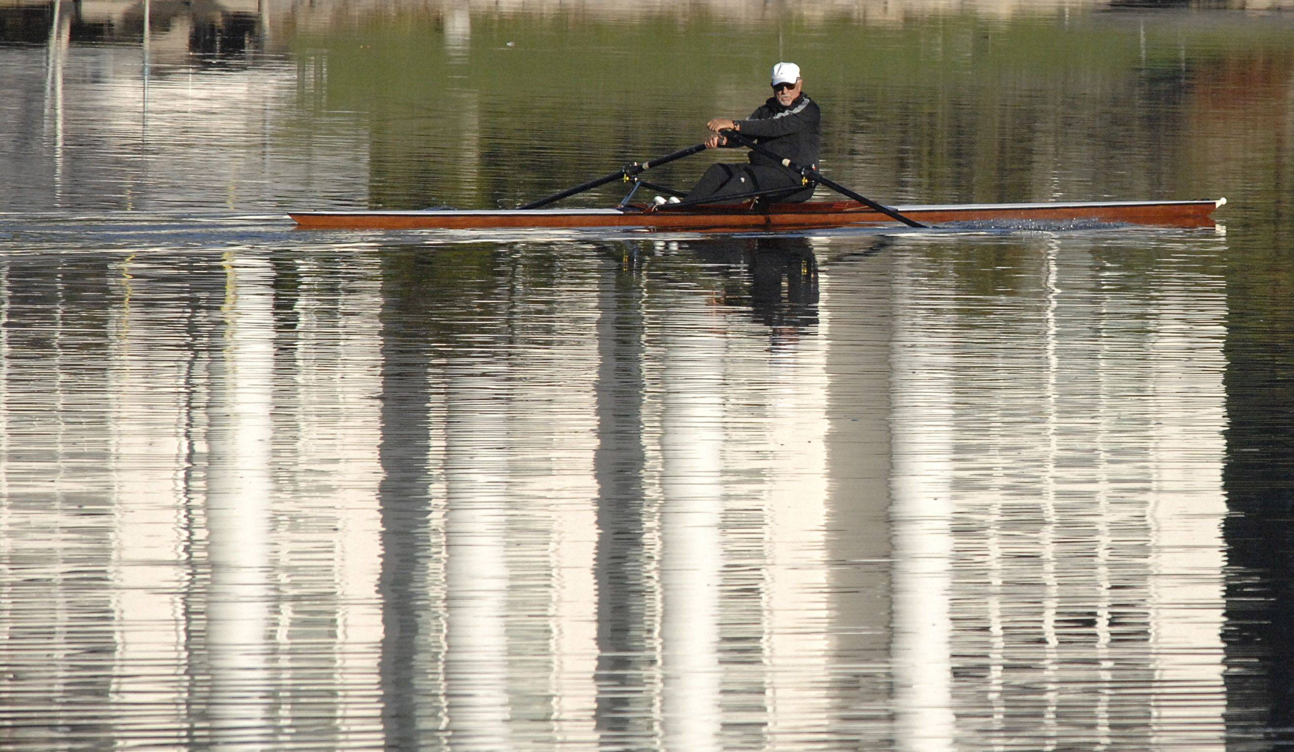 A rower makes his way down the Fox River in Geneva early Wednesday morning, October 6. The white reflected in the water is from a home on the west bank of the river. This type of boat is call a single scull and they are sometimes used for exercise by people who enjoy rowing.