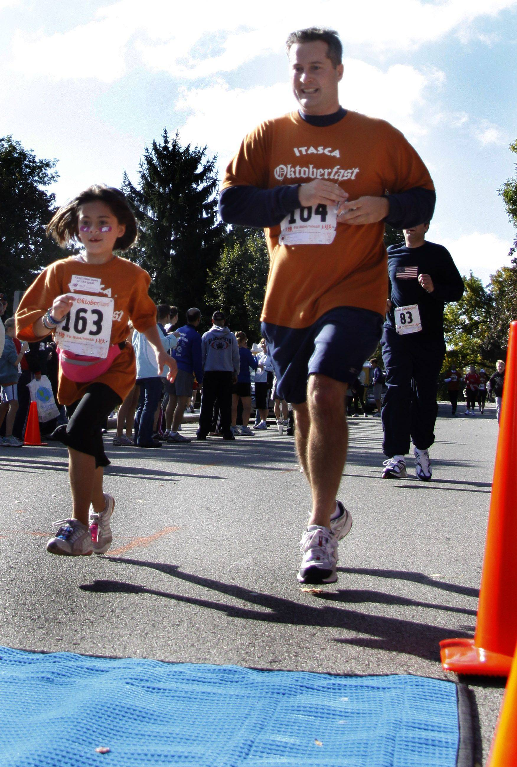 Emma Savage, 8, and her father Brian Savage, both of Itasca stroll to the finish line at Saturdays Oktoberfast 5K Run/Walk. This was the second year the event was held with an estimated $10,000 raised to benefit Marklund, a not-for-profit organization that provides care to those who have severe and profound developmental disabilities.