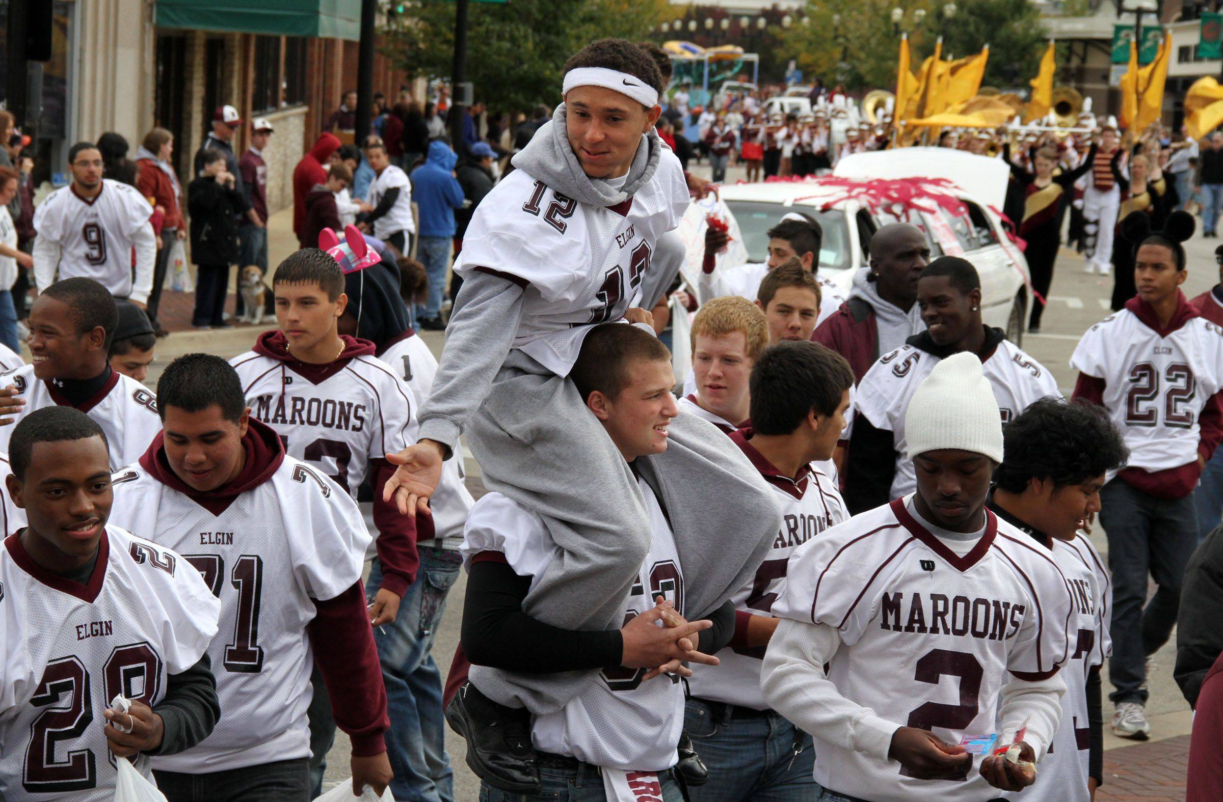 Elgin High School football Lee Jackson looks to pass candy to classmates as he gets a lift east on Chicago Street in Elgin during the school's homecoming parade through downtown Elgin on Sunday, October 3. The parade aslo included the school's marching band, soccer team, volleyball team, and several floats.