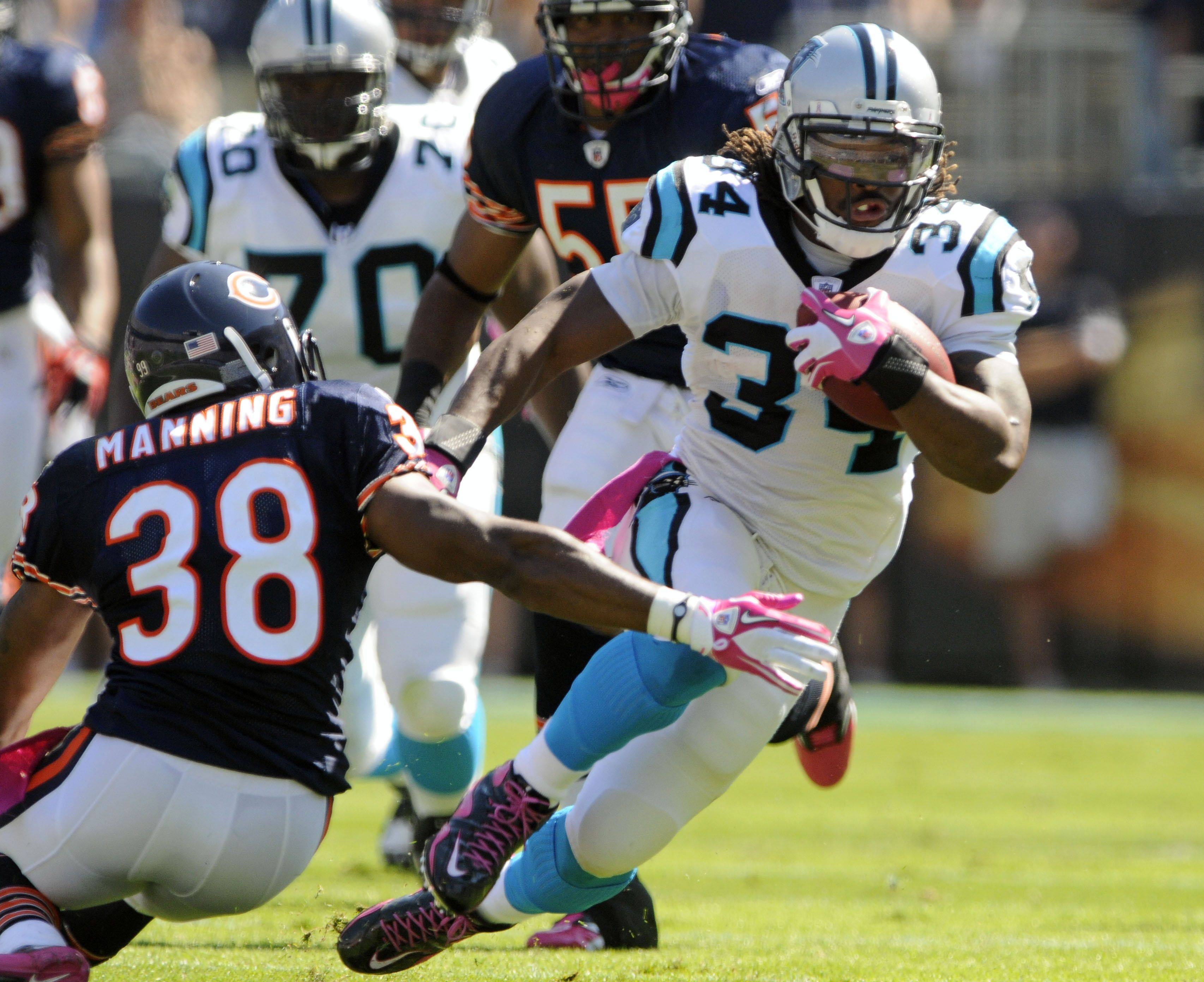Carolina Panthers' DeAngelo Williams runs through the tackle of Chicago Bears' Danieal Manning in the first half.