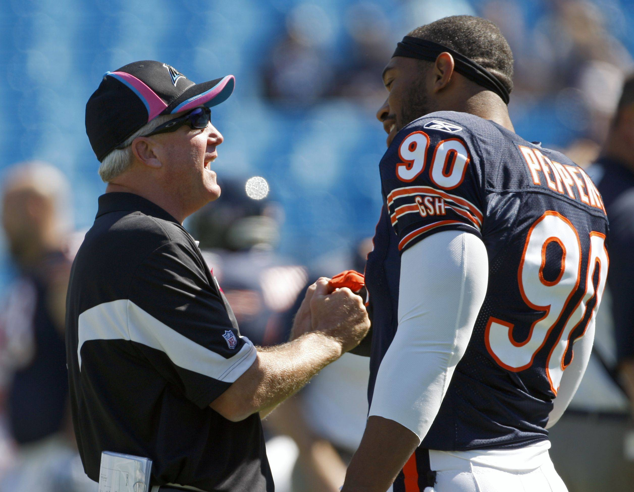 Carolina Panthers coach John Fox, left, talks with Chicago Bears' Julius Peppers .