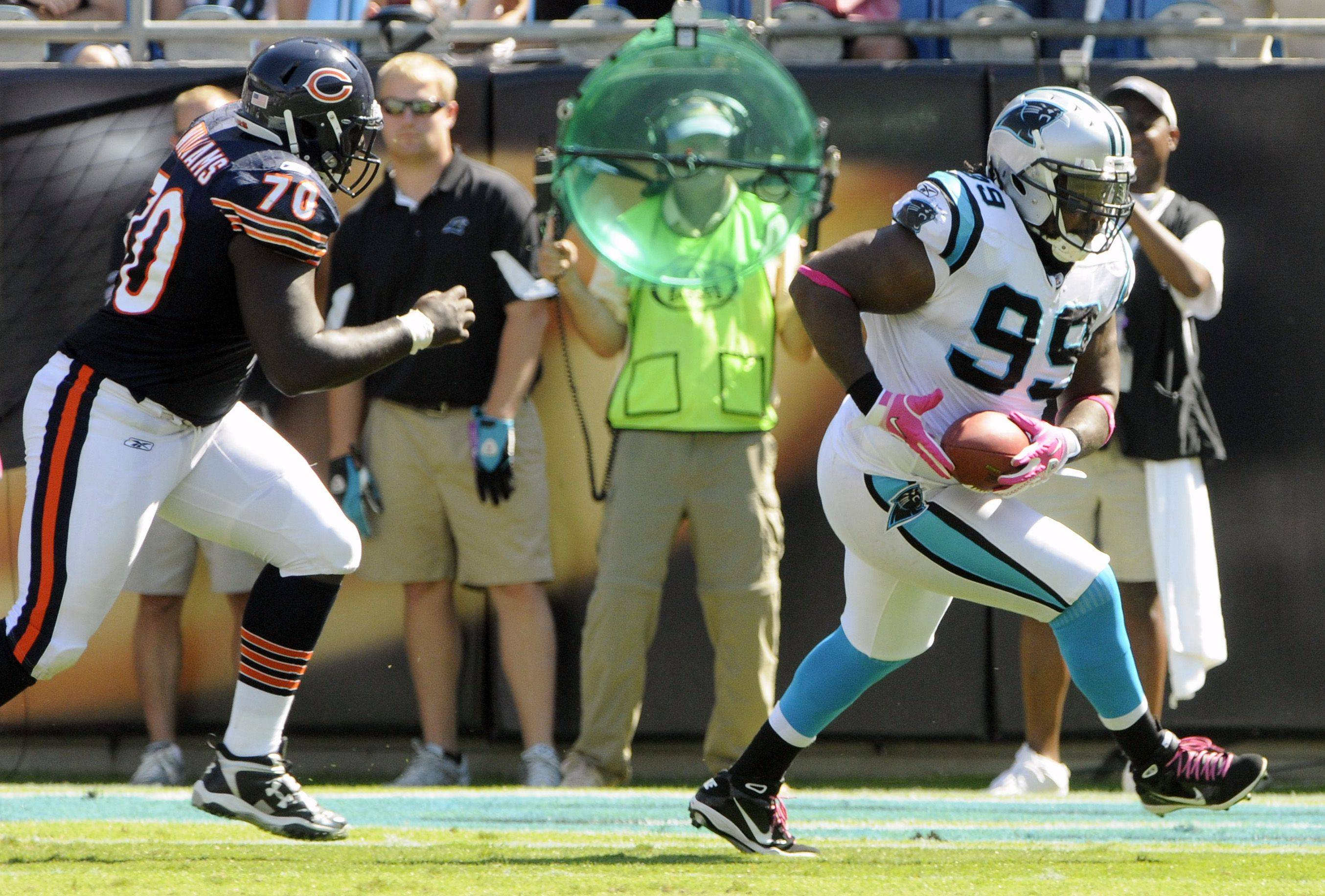 Carolina Panthers' Ed Johnson runs after intercepting a pass as Chicago Bears' Edwin Williams pursues in the first half.