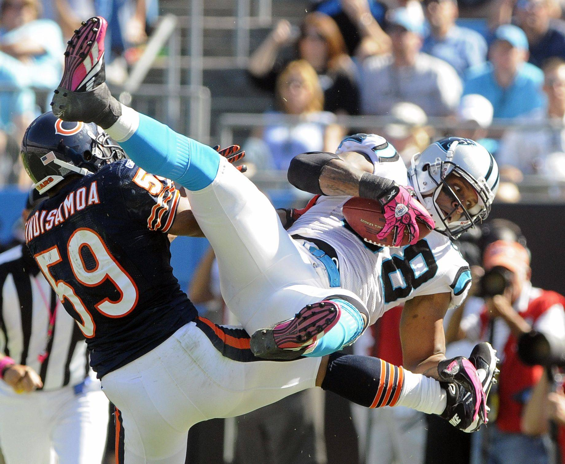 Carolina Panthers' Dante Rosario is upended by Chicago Bears' Pisa Tinoisamoa in the second half.