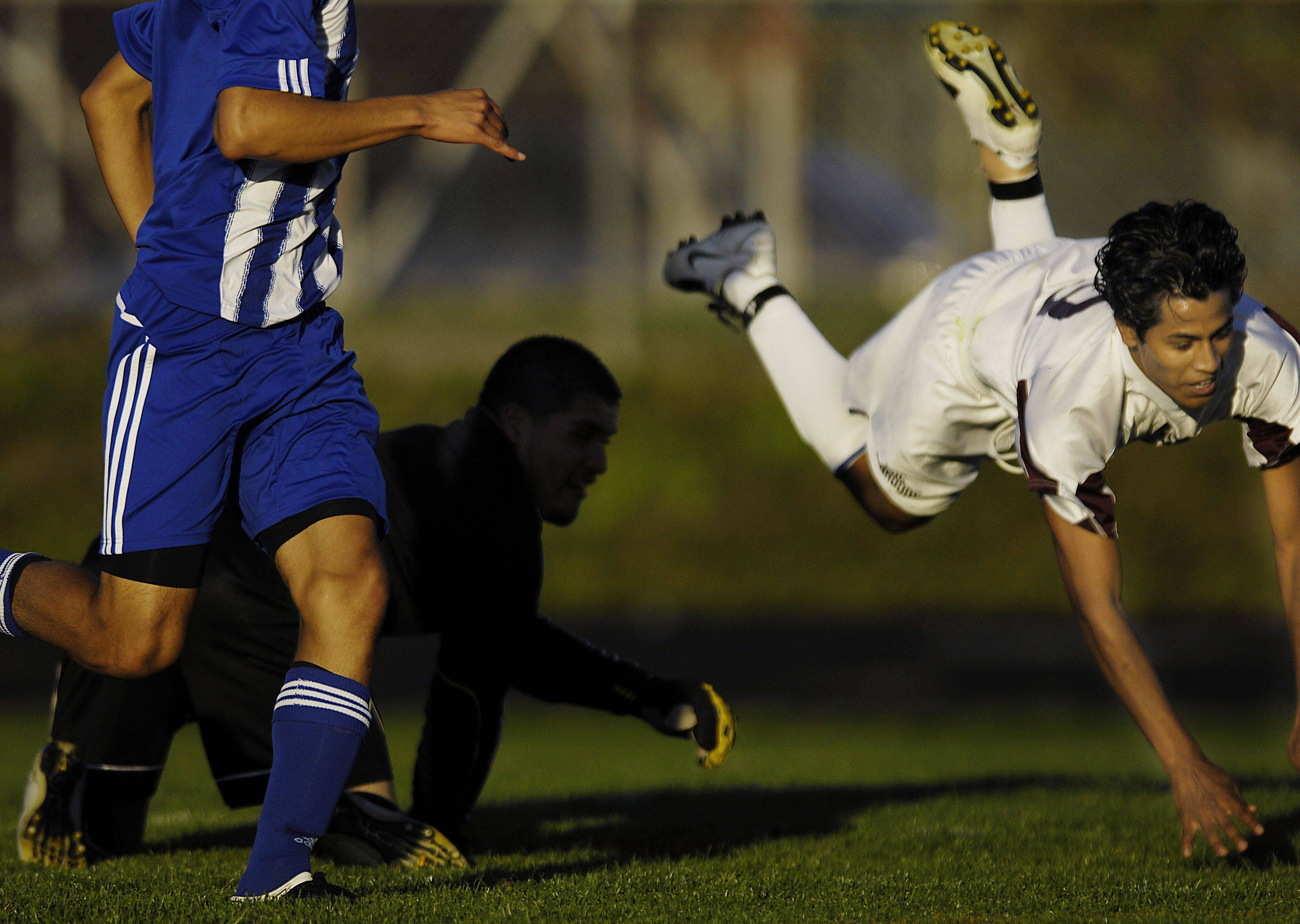 Larkin goalkeeper Santiago Guerrero upends Elgin midfielder Samual Escobar Tuesday as he charged the net late in the game.