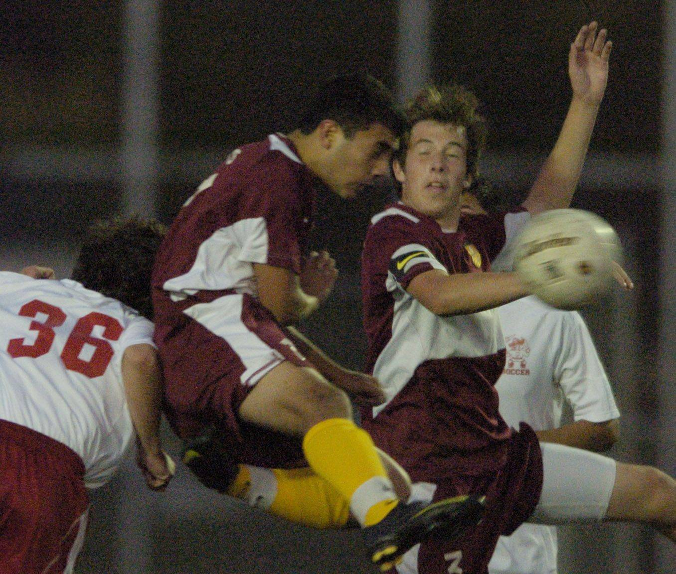 Schaumburg's Gus Alvarez, middle, gets the header between Palatine's Kyle Clancy and teammate Joey Faleni.