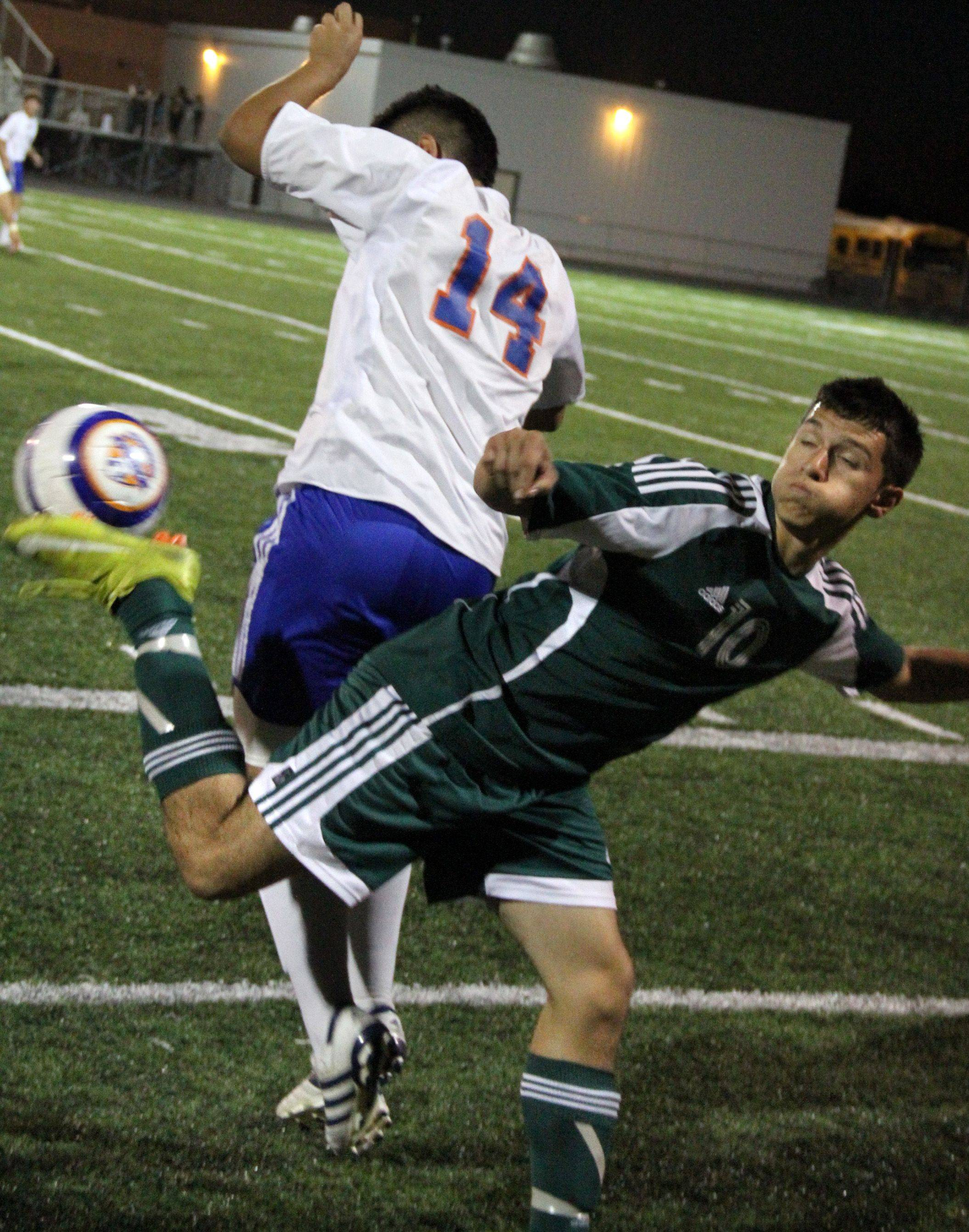 Elk Grove's Cesar Rodriguez kicks the ball from behind as he battles Hoffman Estates' Gilberto Cuellar for position Thursday.