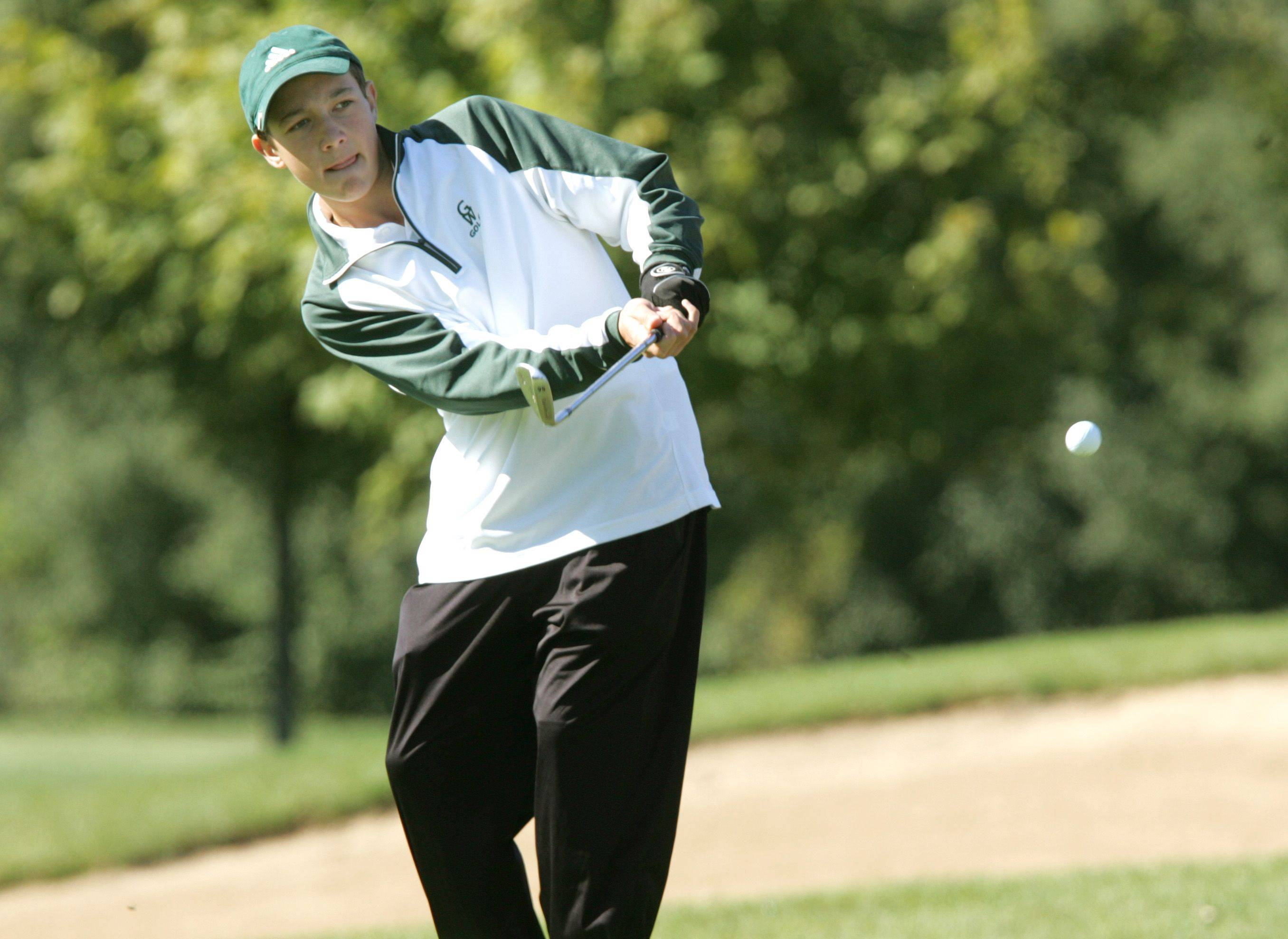 Glenbard West's Pete Norgaard hits his approach shot during the Wheaton Warrenville South boys golf regional at the Arrowhead Golf Course.