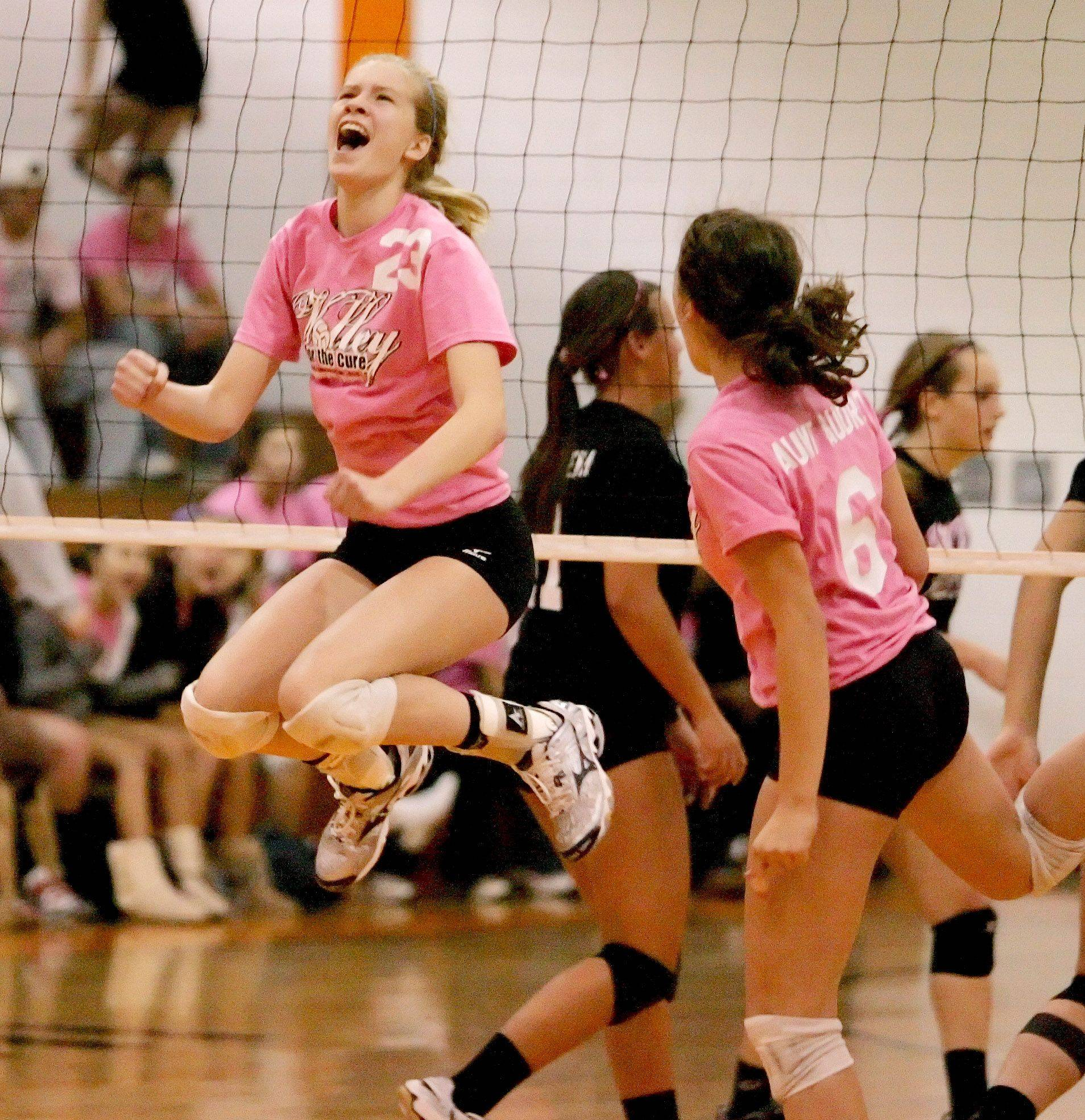 Sammy Condon of Naperville Central leaps into the air celebrating a point won against Wheaton Warrenville South during girls volleyball action Tuesday in Wheaton.