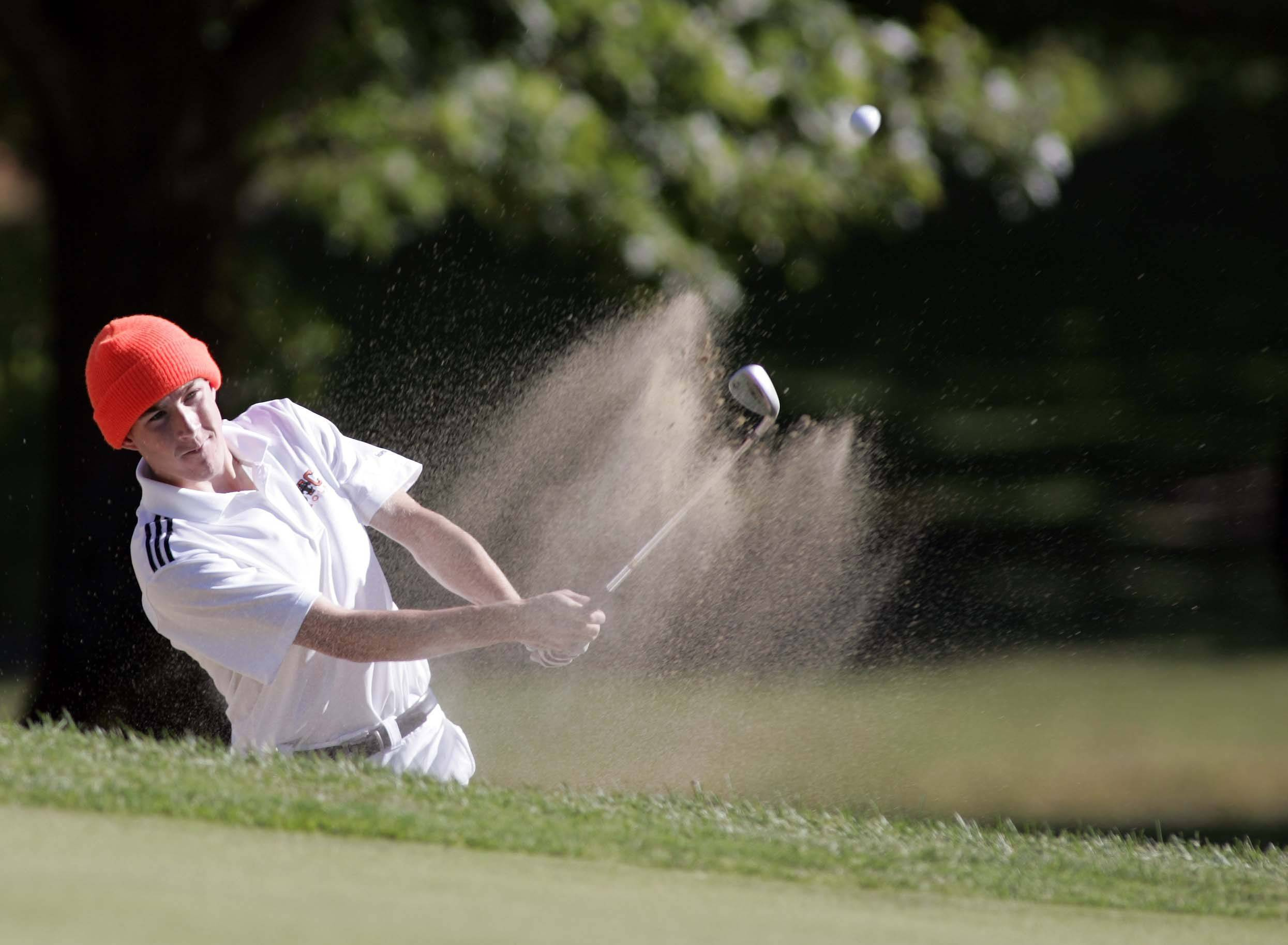 St. Charles East's Jordan Wetsch hits out of the sand during the Larkin regional boys golf tournament at Bartlett Hills Tuesday.