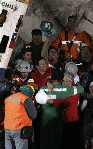 The last rescued miner, Luis Urzua, center wearing green, hugs Chile's  President Sebastian Pinera after being rescued from the collapsed San Jose gold and copper mine where he had been trapped with 32 other miners for over two months near Copiapo, Chile, Wednesday.