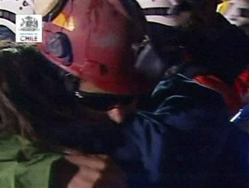 In this photo from TV, Florencio Avalos, the first miner to be rescued, center, is greeted after his rescue Tuesday at San Jose Mine near Copiapo, Chile.