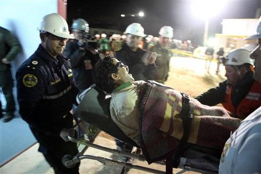 In this photo released by the Chilean government, miner Juan Illanes is carried away on a stretcher after being rescued from the collapsed San Jose gold and copper mine where he was trapped with 32 other miners for over two months near Copiapo, Chile, early Wednesday.