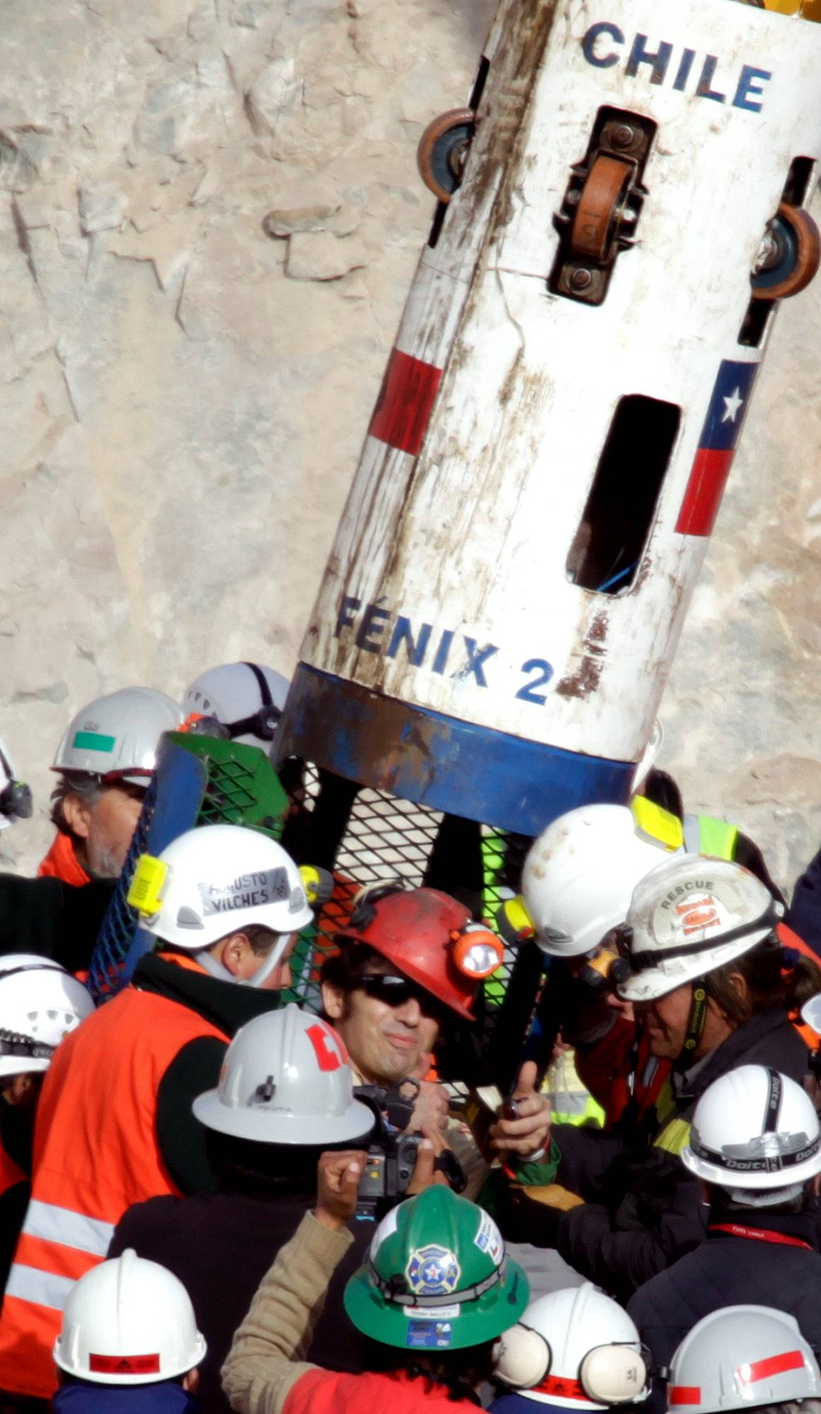 Miner Alex Vega Salazar, center, gives a thumbs up after emerging from the capsule that brought him to the surface from the collapsed San Jose gold and copper mine near Copiapo, Chile, Wednesday. Vega is the tenth of 33 miners who was rescued from the mine after more than 2 months trapped underground.
