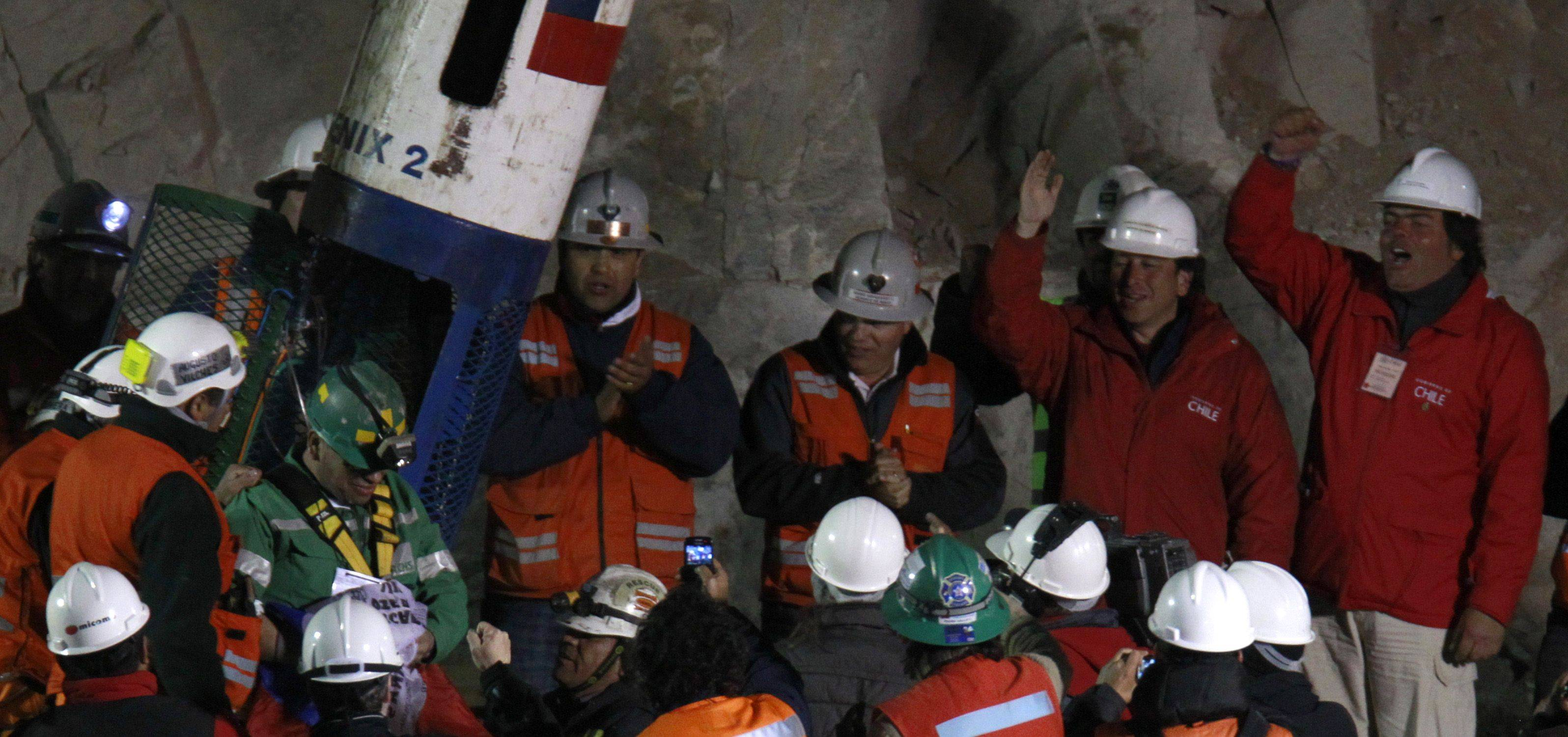 Rescued miner Jose Ojeda, second from left wearing green, exists the capsule that brought him to the surface from the collapsed San Jose gold and copper mine where he was trapped with 32 other miners for over two months near Copiapo, Chile, early Wednesday Oct. 13, 2010.
