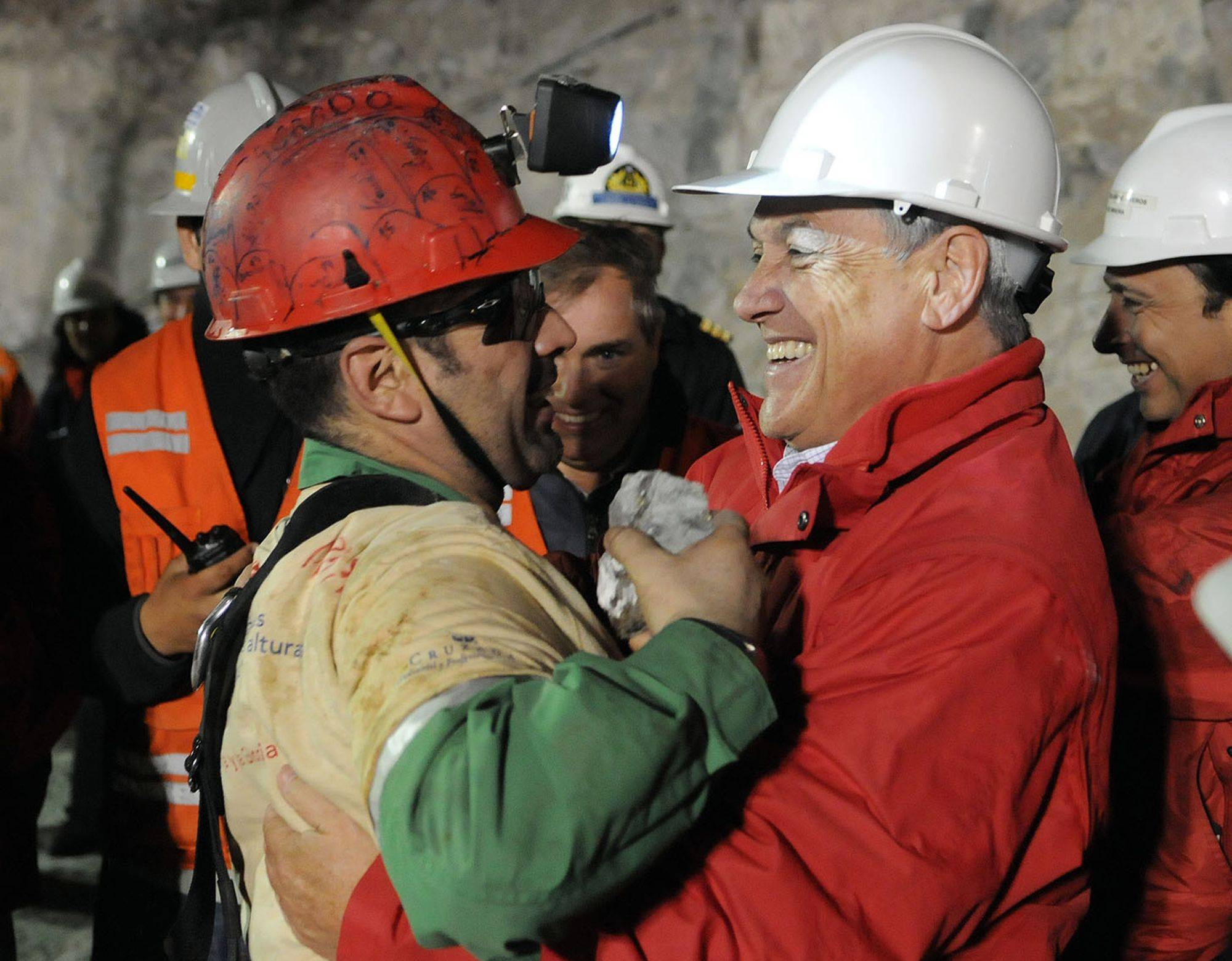 In this photo released by the Chilean presidential press office, Chile's President Sebastian Pinera, right, hugs rescued miner Mario Sepulveda after Sepulveda was rescued from the collapsed San Jose gold and copper mine where he was trapped with 32 other miners for over two months near Copiapo, Chile, early Wednesday, Oct. 13, 2010.
