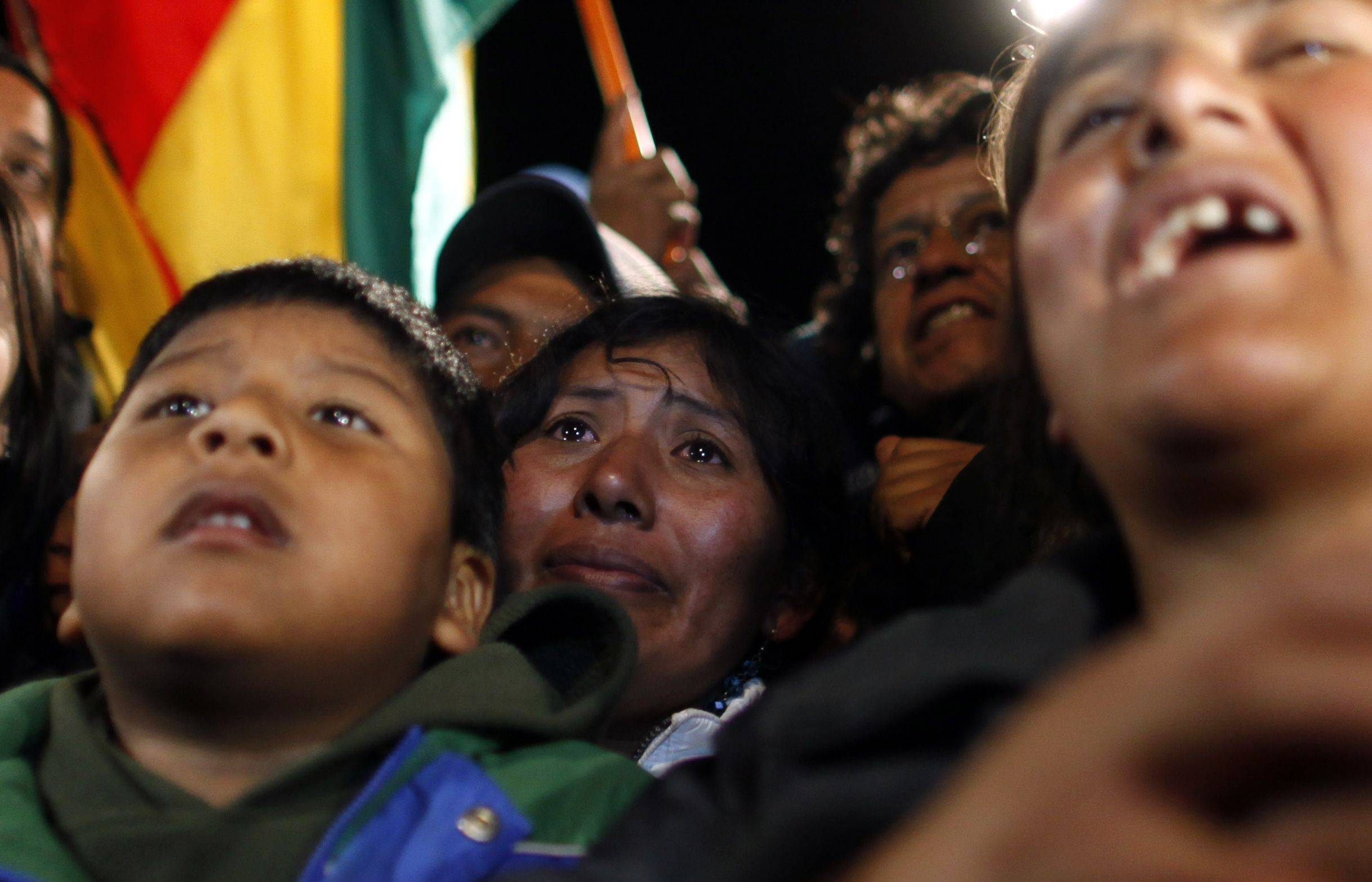 Relatives of trapped Bolivian miner Carlos Mamani Solis react while watching his rescue on a TV screen at the camp outside the San Jose mine near Copiapo, Chile, early Wednesday, Oct. 13, 2010. Mamani was trapped with 32 other miners for over two months in the collapsed mine.