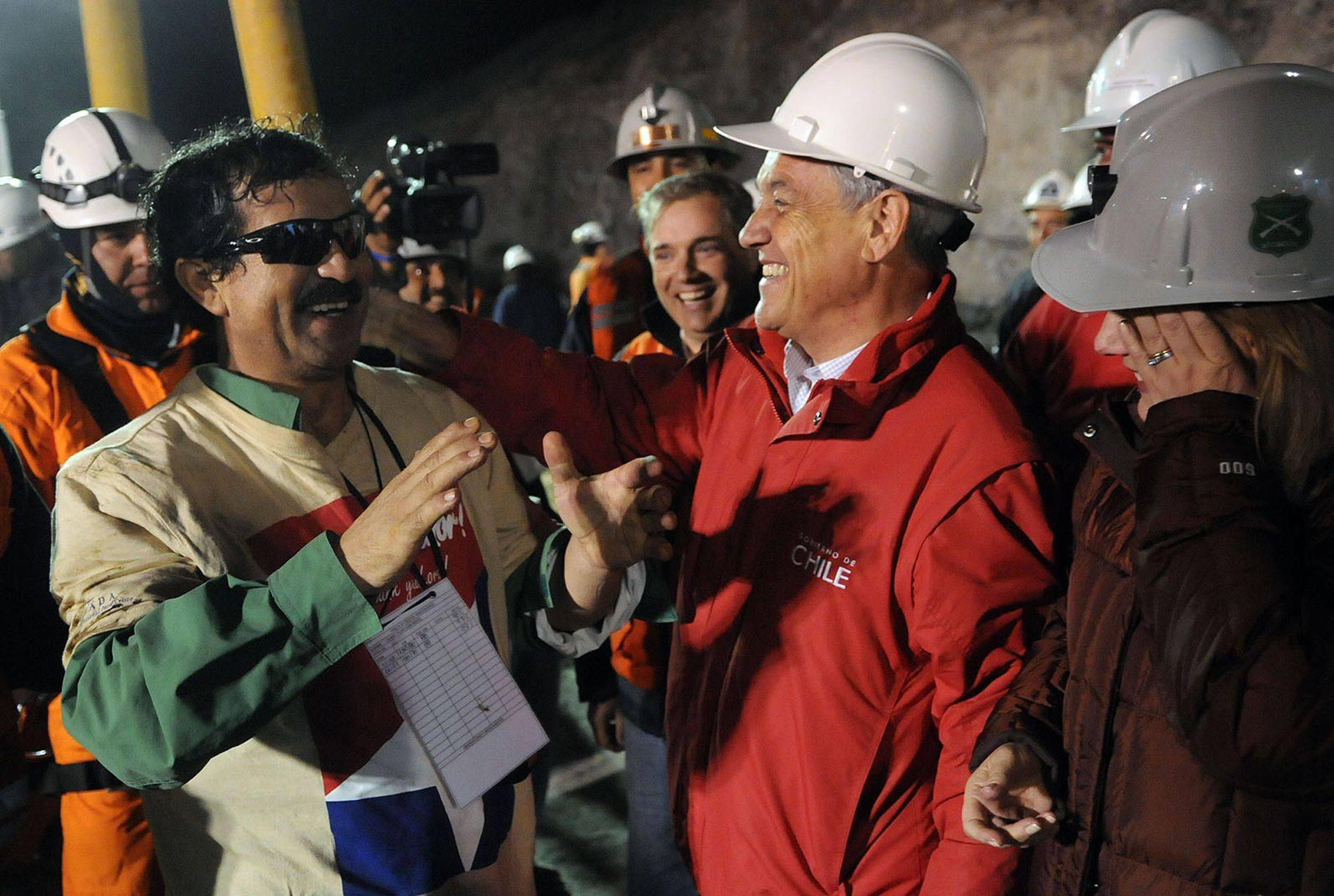 In this photo released by the Chilean presidential press office, miner Juan Illanes, left, greets Chile's President Sebastian Pinera after being rescued from the collapsed San Jose gold and copper mine where he was trapped with 32 other miners for over two months near Copiapo, Chile, early Wednesday Oct. 13, 2010.