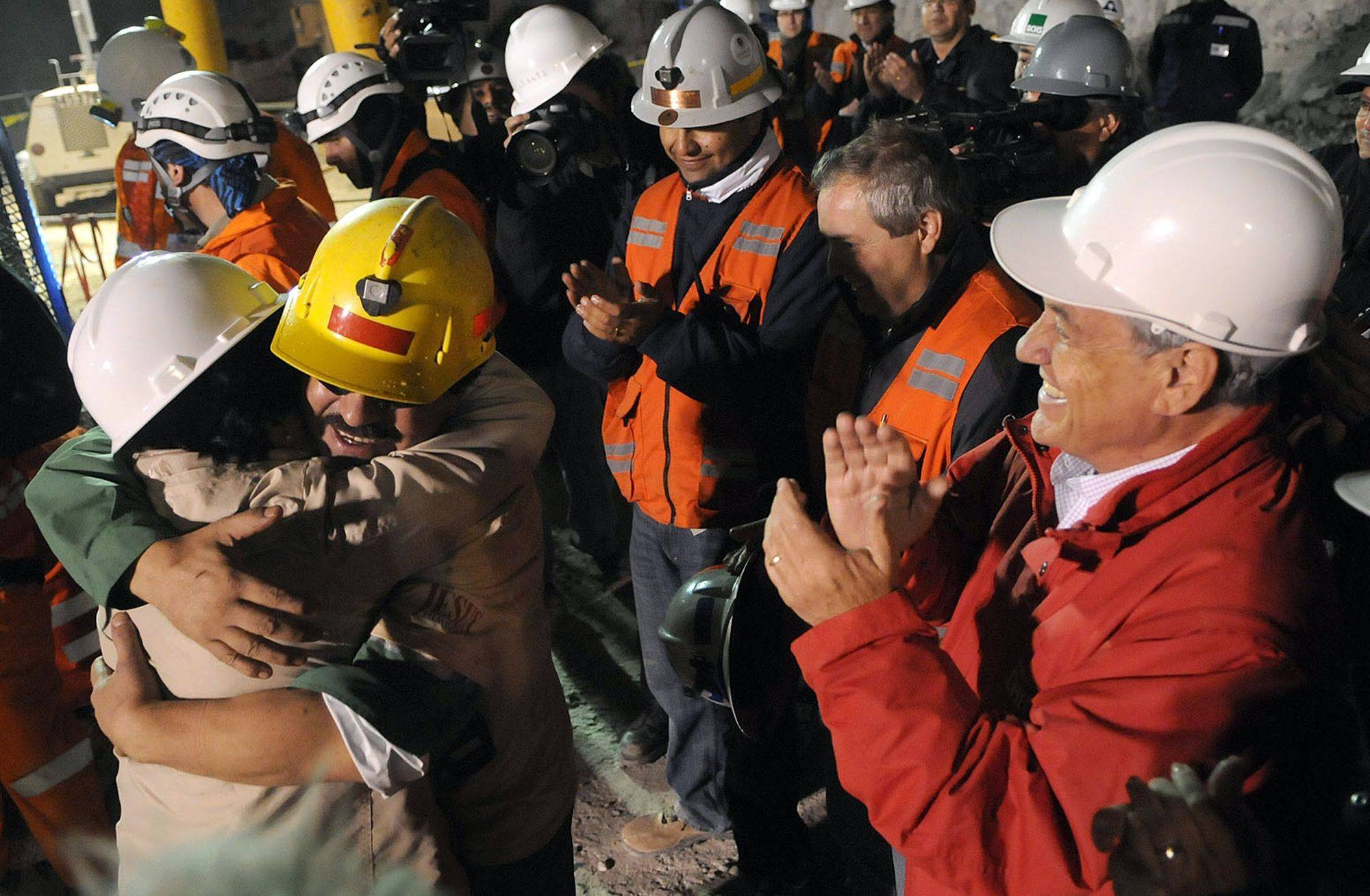 In this photo released by the Chilean presidential press office, miner Juan Illanes, second right, hugs his wife, name unavailable, as Chile's President Sebastian Pinera applauds, after after being rescued from the collapsed San Jose gold and copper mine where he was trapped with 32 other miners for over two months near Copiapo, Chile, early Wednesday, Oct. 13, 2010.