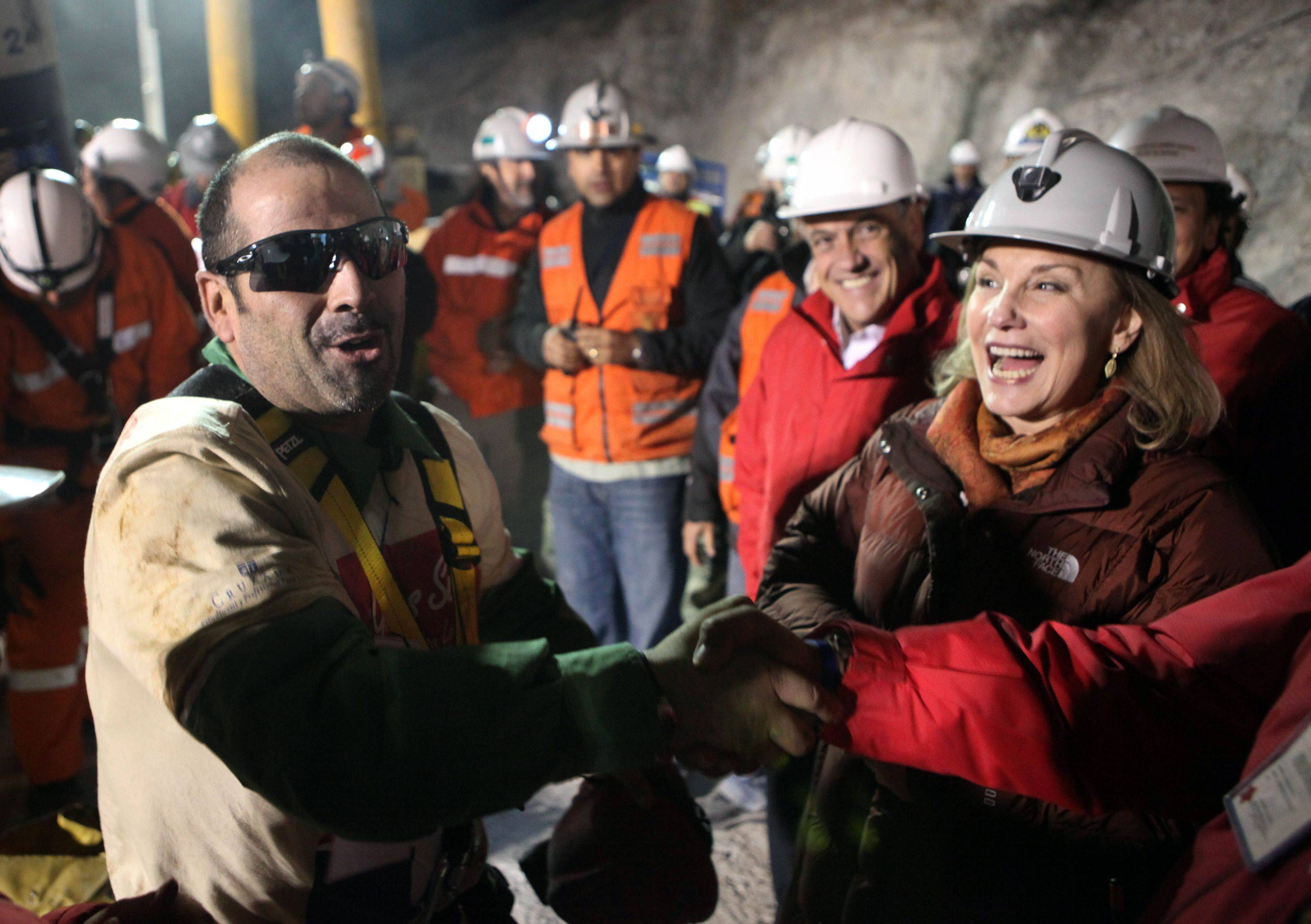 In this photo released by the Chilean government, miner Mario Sepulveda, left, shakes hands with an official as Chilean first lady Cecilia Morel and President Sebastian Pinera, second right, look on, after being rescued from the collapsed San Jose gold and copper mine where he was trapped with 32 other miners for over two months near Copiapo, Chile, early Wednesday, Oct. 13, 2010.