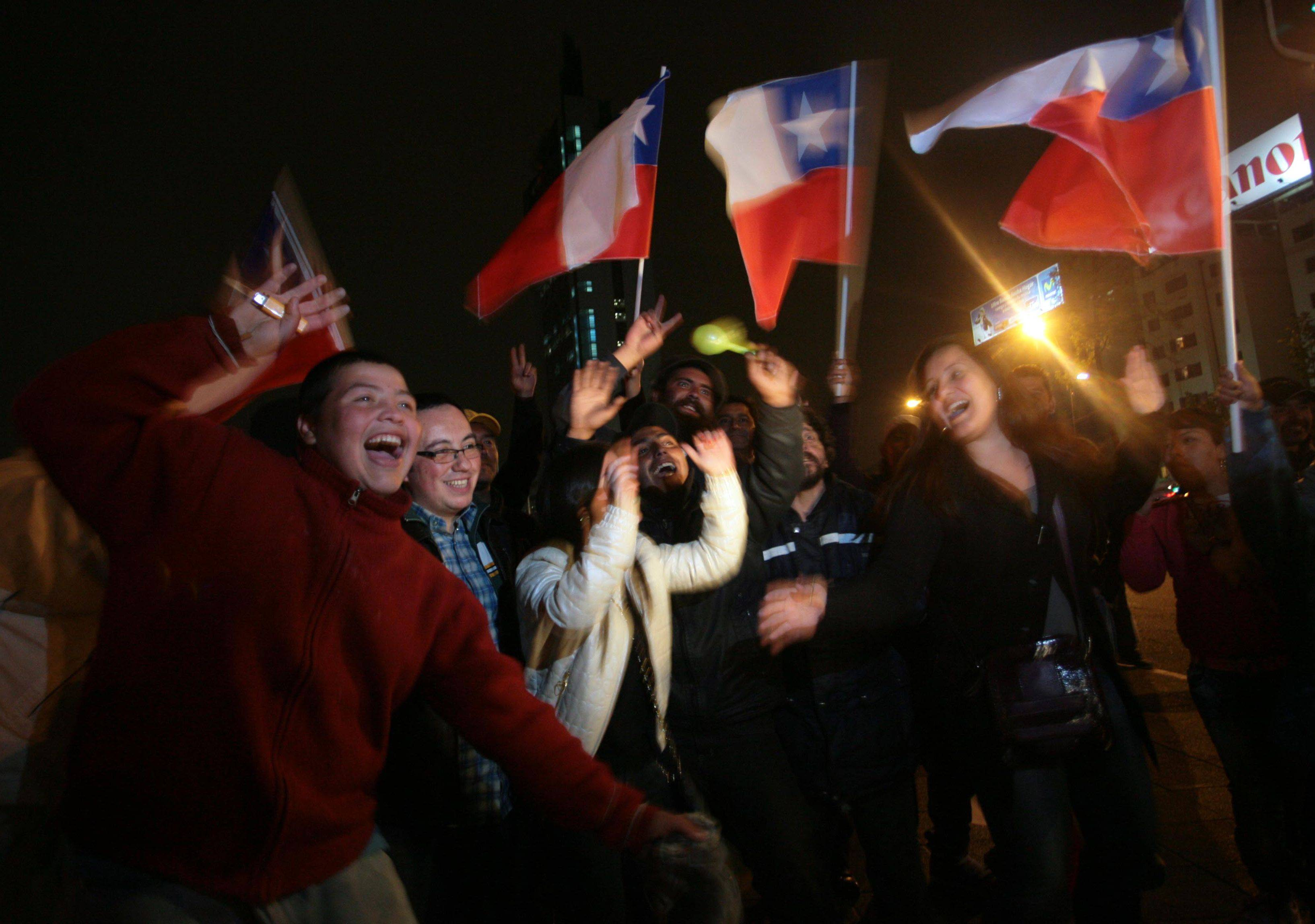 People celebrate in the streets of Santiago, the capital of Chile, after the first trapped miner Florencio Avalos was rescued from the San Jose gold and copper mine near Copiapo, early Wednesday, Oct. 13, 2010.