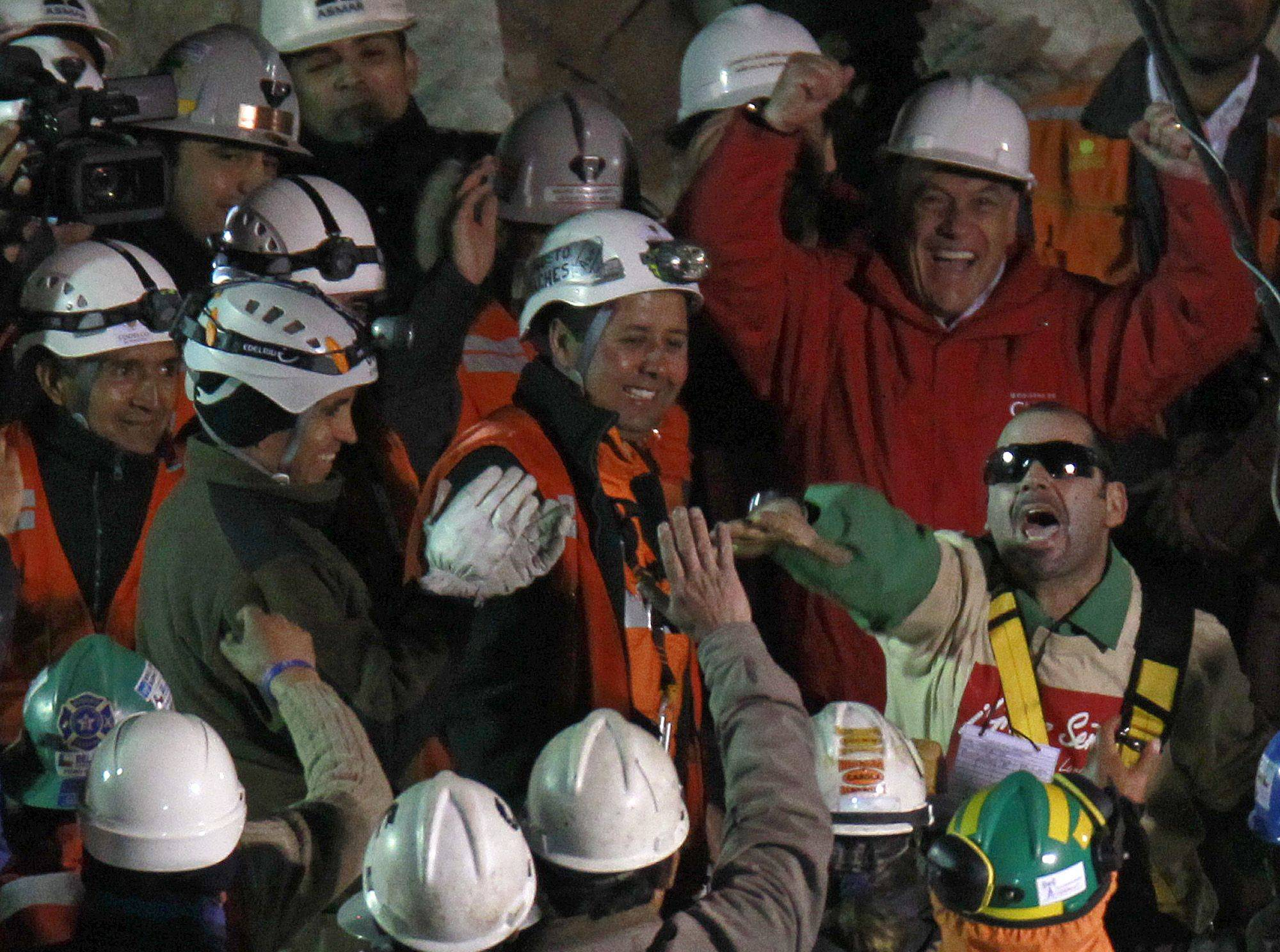 Chile's President Sebastian Pinera, top right, cheers as rescued miner Mario Sepulveda Espina, right, salutes after being rescued from the the collapsed San Jose gold and copper mine where he was trapped with 32 other miners for over two months near Copiapo, Chile, early Wednesday Oct. 13, 2010.