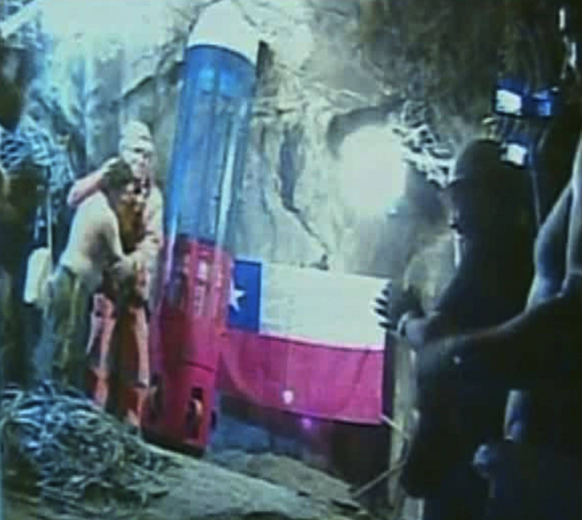 In this screen grab taken from video, rescuer Manuel Gonzalez Pavez, second left, is greeted by the trapped miners, Tuesday, Oct. 12, 2010 at San Jose Mine near Copiapo, Chile.