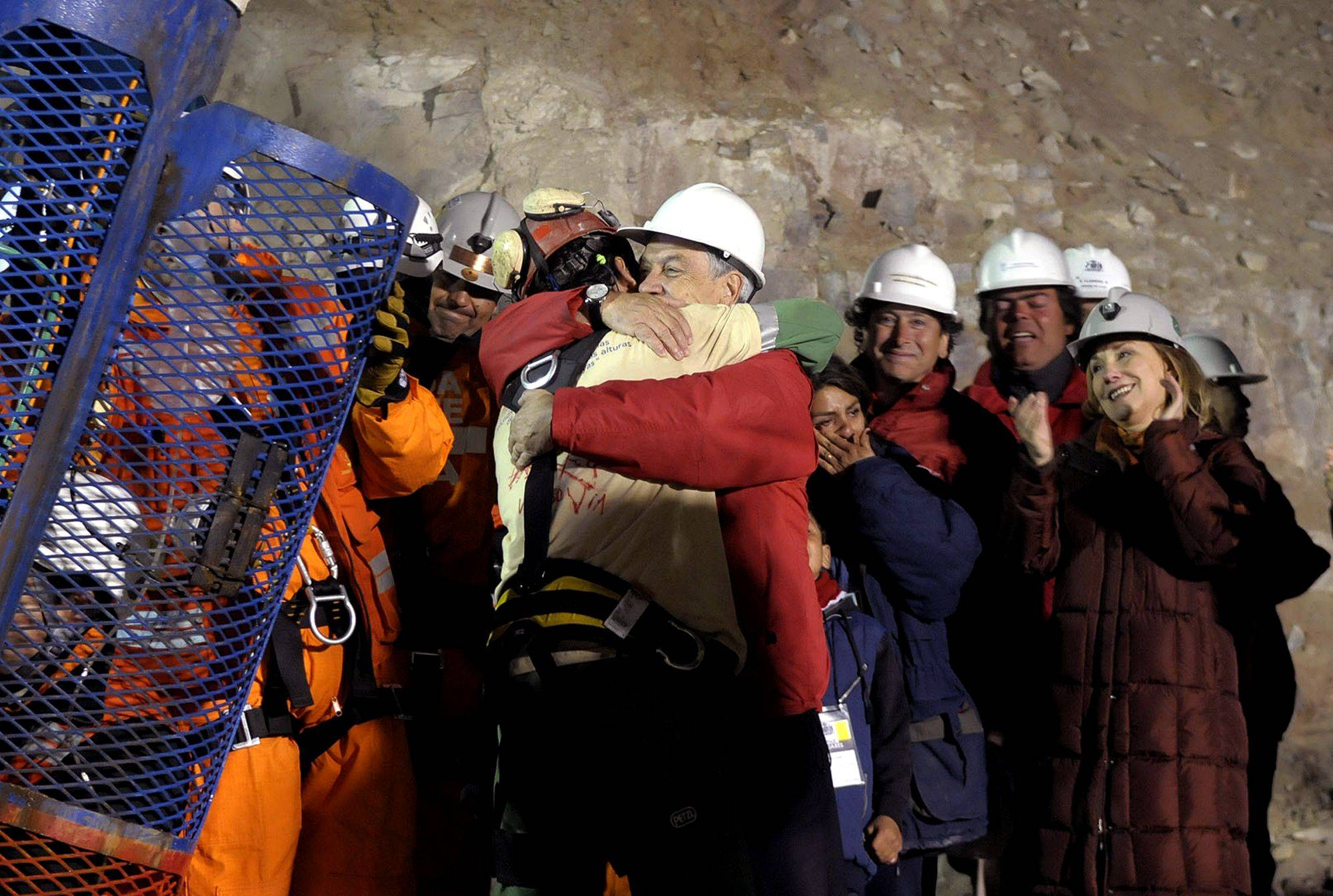 In this photo released by the Chilean presidential press office, Chile's President Sebastian Pinera, front right, hugs rescued miner Florencio Avalos after Avalos was rescued from the collapsed San Jose gold and copper mine where he was trapped with 32 other miners for over two months near Copiapo, Chile, Tuesday Oct. 12, 2010.