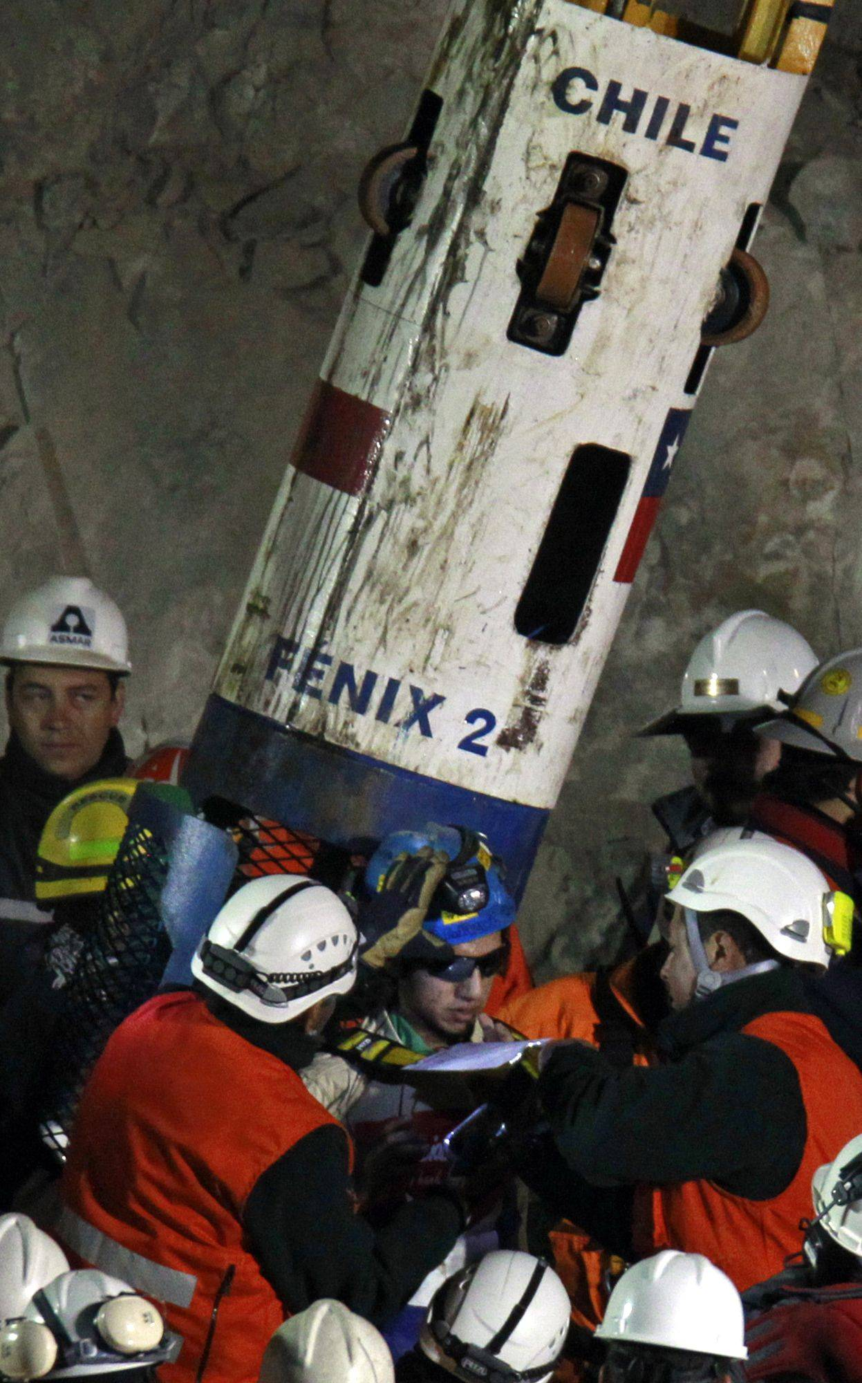 Miner Jimmy Sanchez, bottom center, is helped out of the capsule after being rescued from the collapsed San Jose gold and copper mine where he was trapped with 32 other miners for over two months near Copiapo, Chile, early Wednesday Oct. 13, 2010.