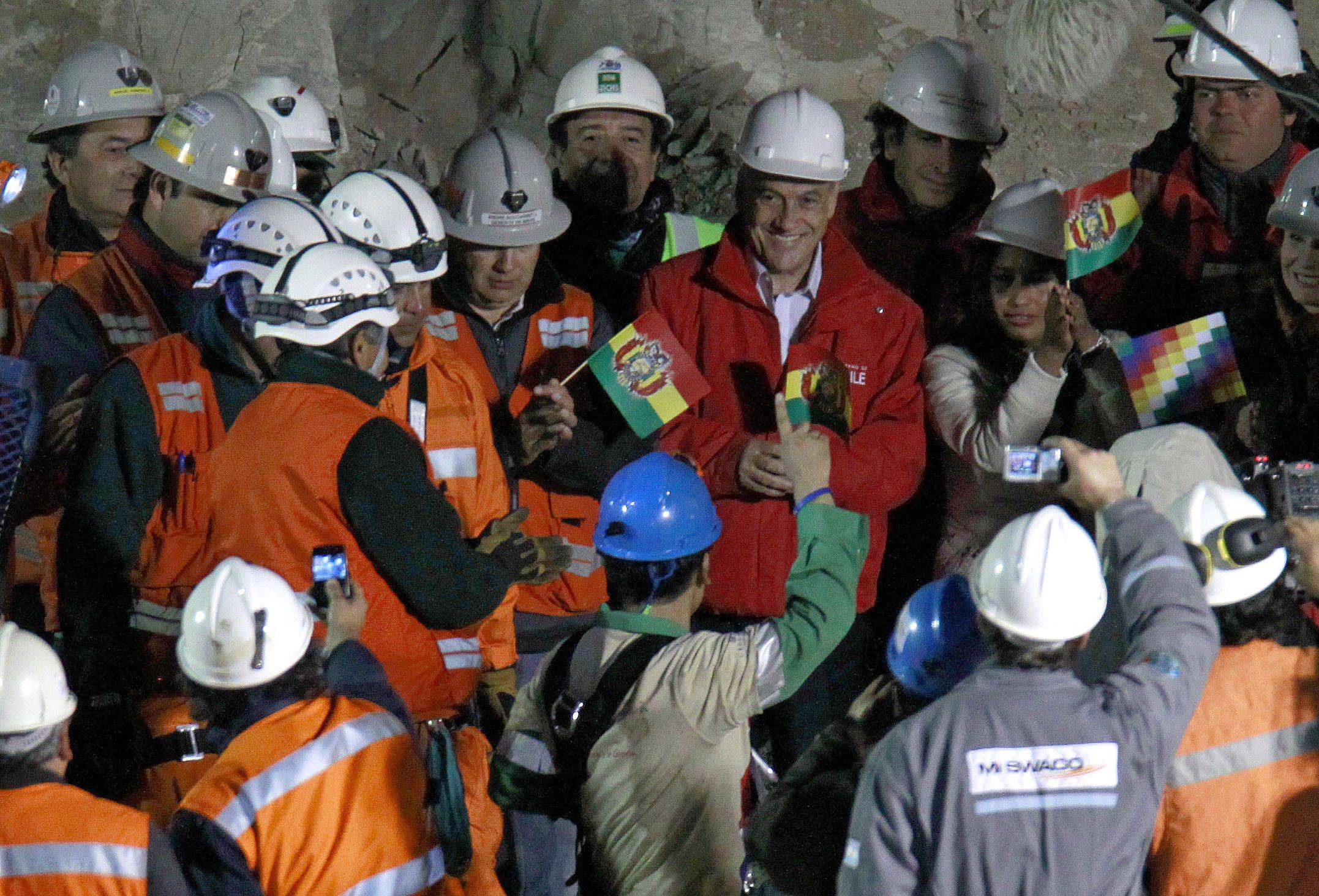 Rescued miner Carlos Mamani Solis, from Bolivia, bottom center, greets Chile's President Sebastian Pinera, top wearing red jacket and holding a Bolivian flag, after being rescued from the collapsed San Jose gold and copper mine where he was trapped with 32 other miners for over two months near Copiapo, Chile, early Wednesday Oct. 13, 2010.